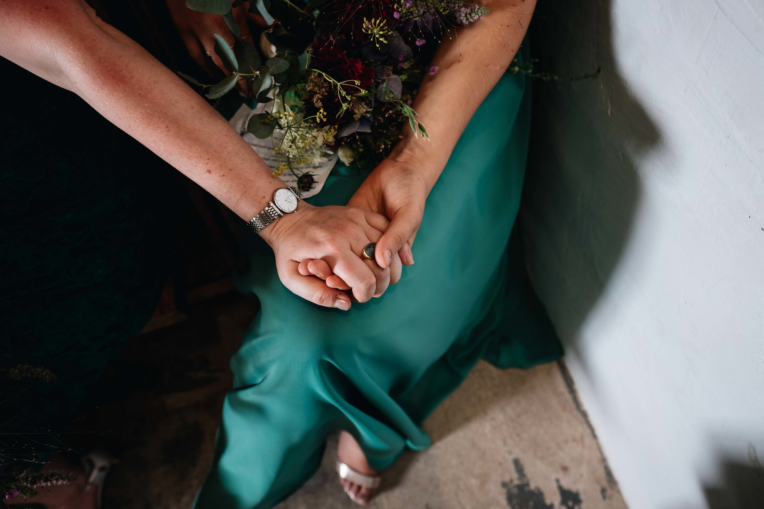 two guests holding hands during wedding ceremony
