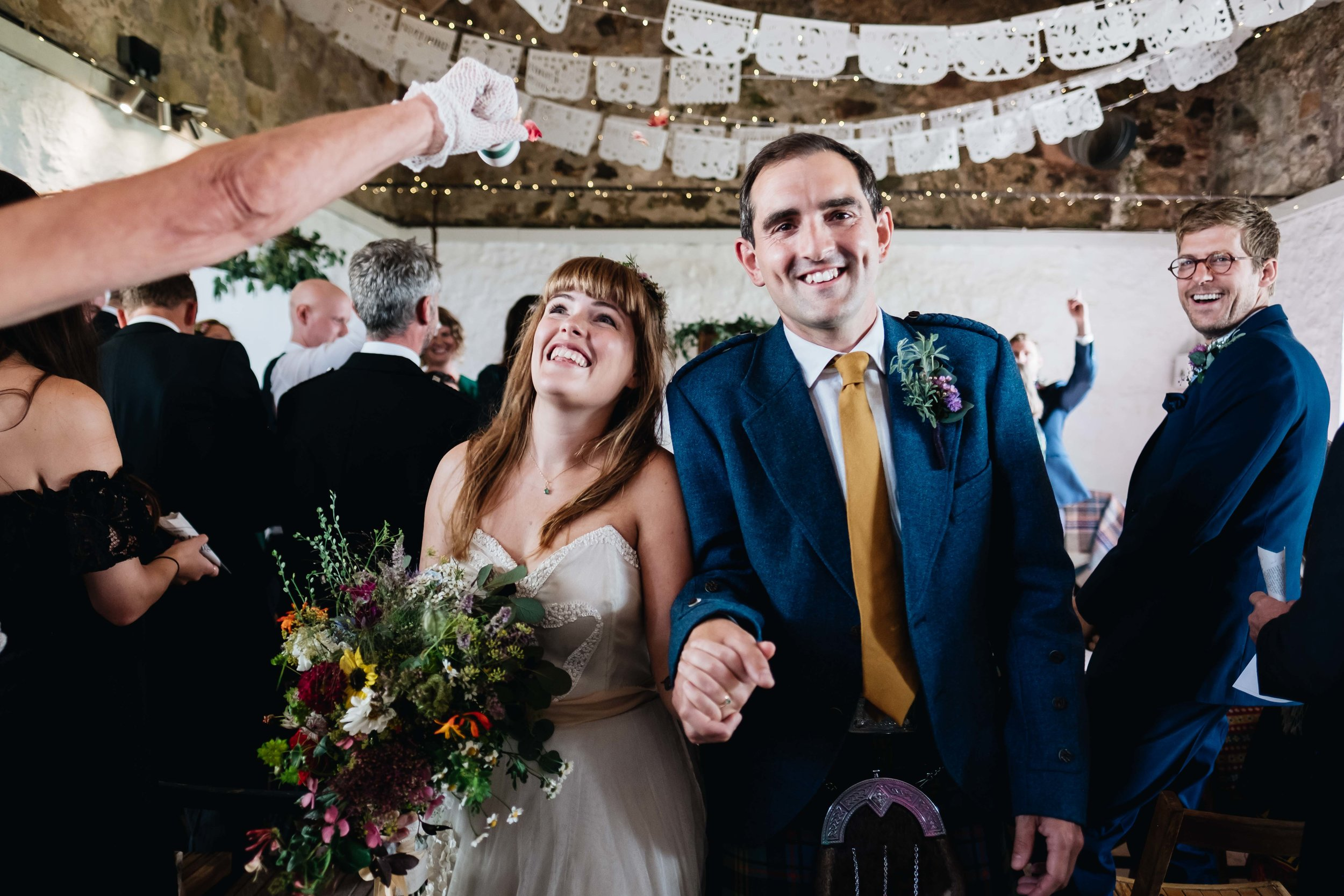 guests throwing confetti as bride and groom walking down the aisle