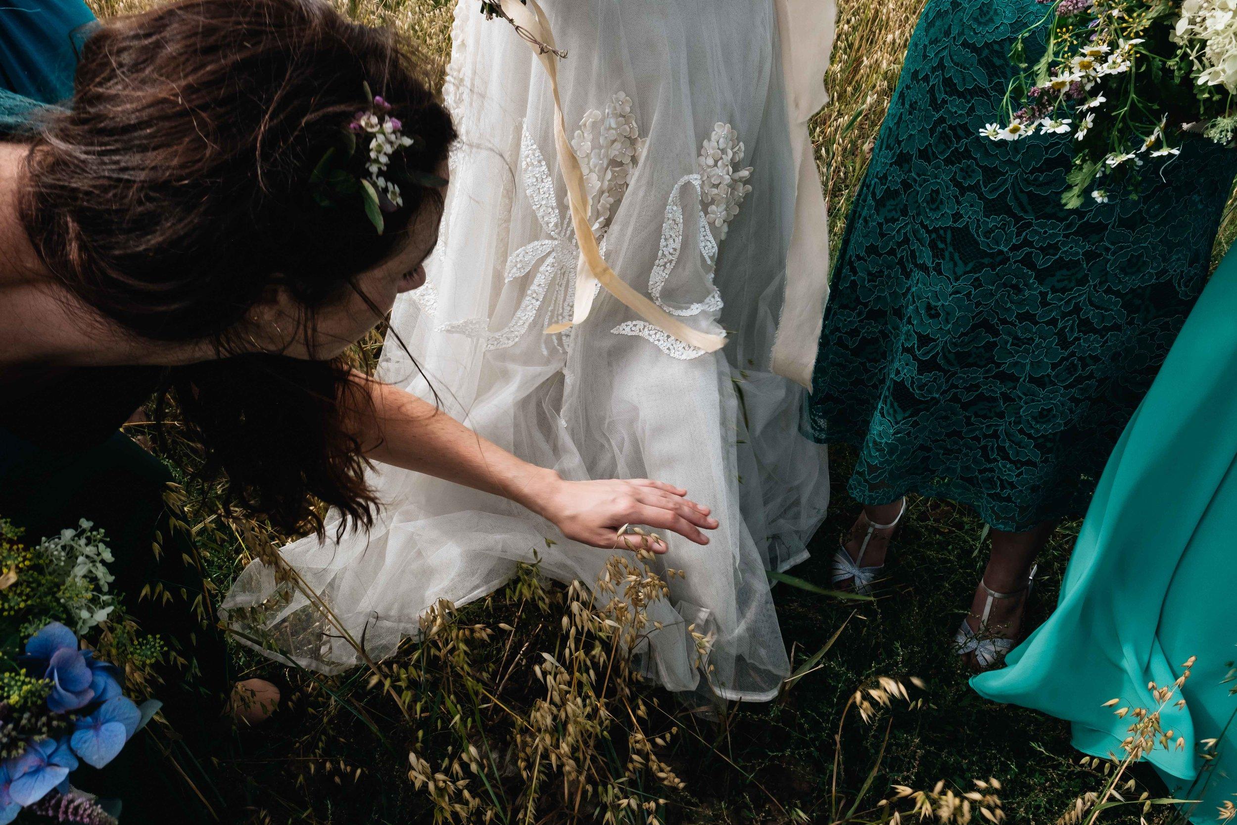 bridesmaid helping loosen bride's dress that's stuck on grass