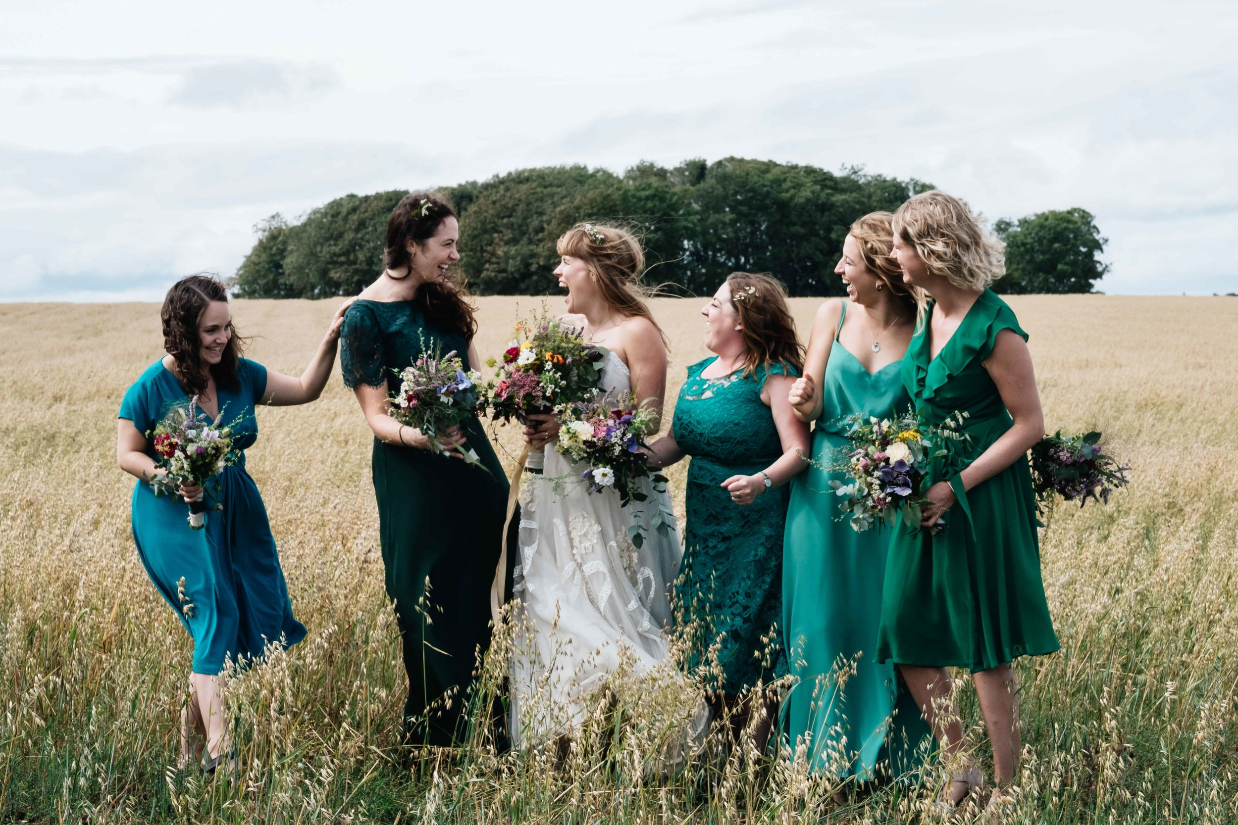 bridesmaids standing in a field laughing