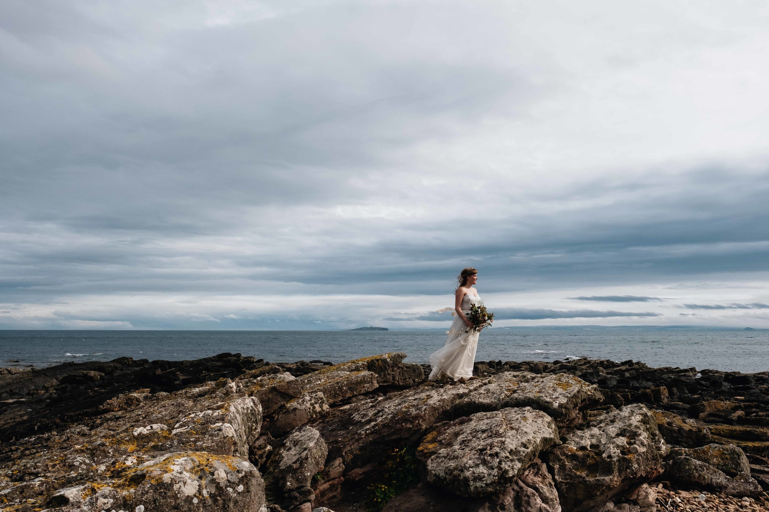 bride standing on a rock