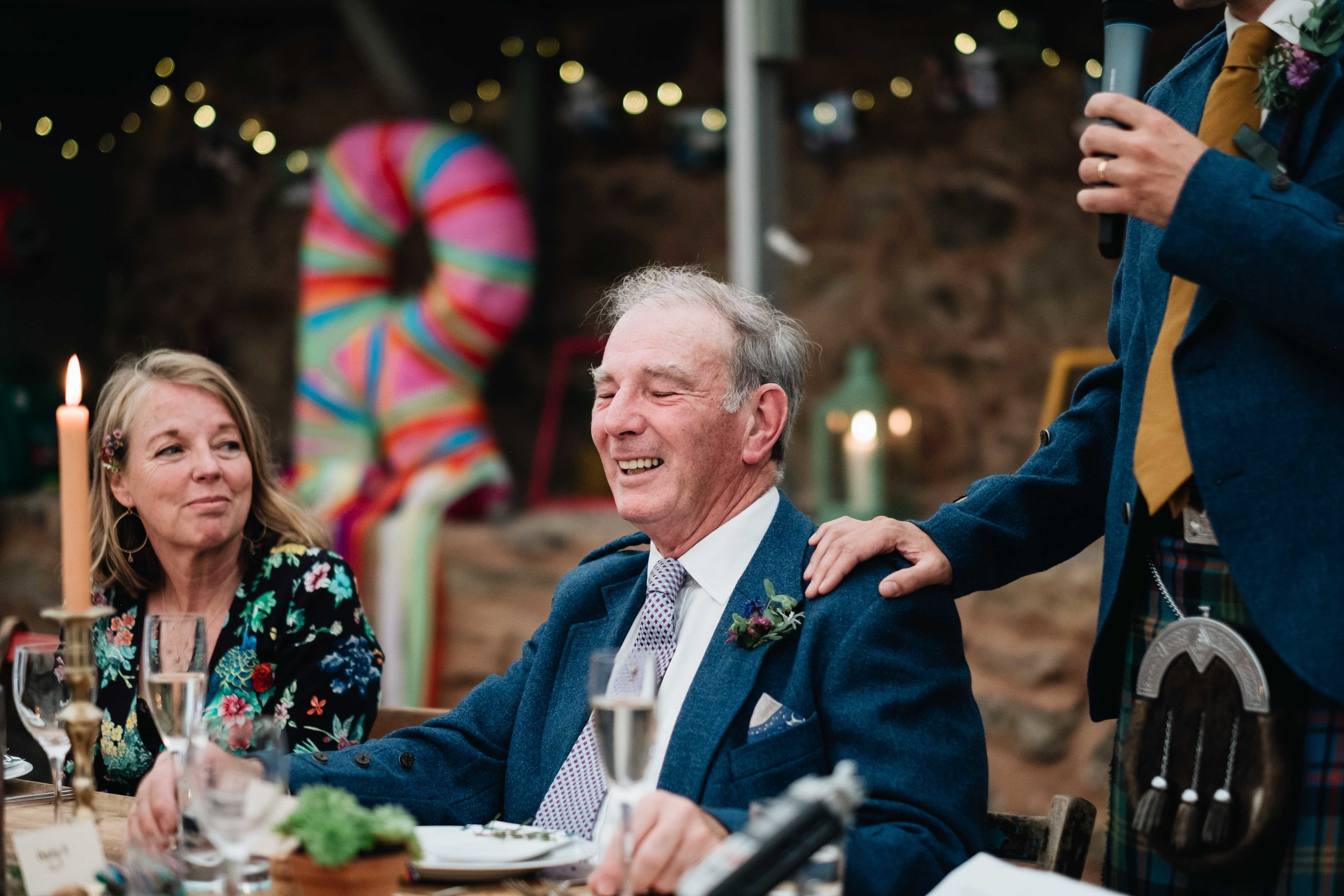 father laughing at something his son has said during the wedding speech