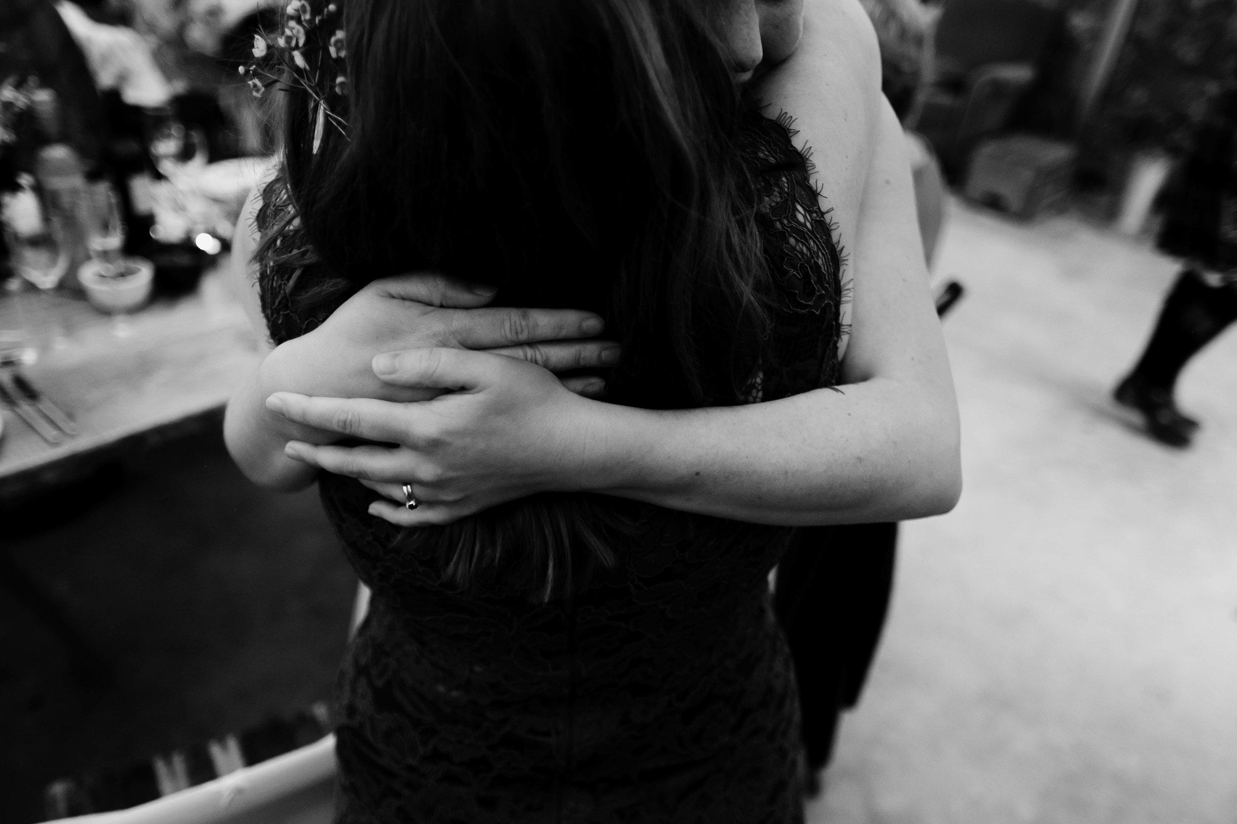 a close friend hugs the bride