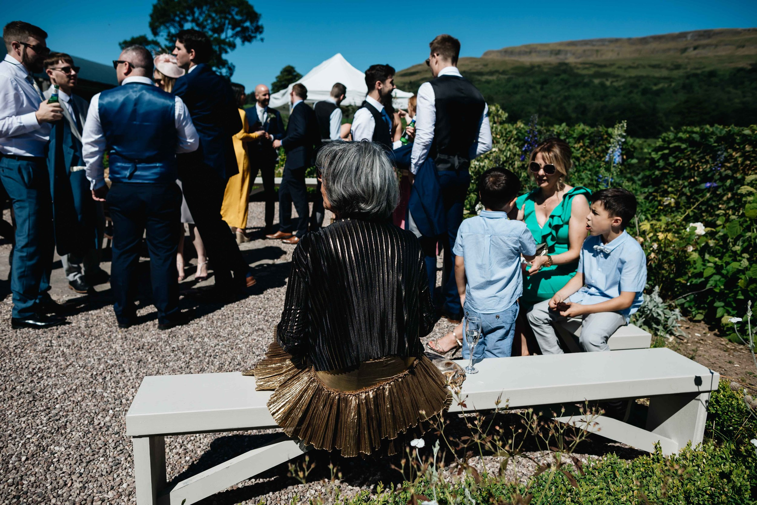 wedding guest with gold skirt sits on bench