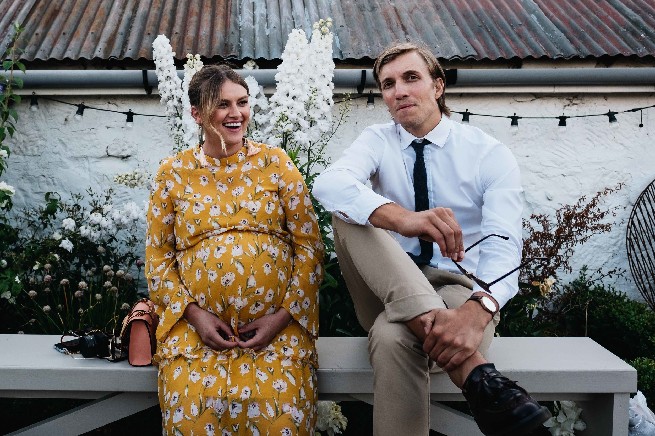 pregnant guest and partner sitting on a bench