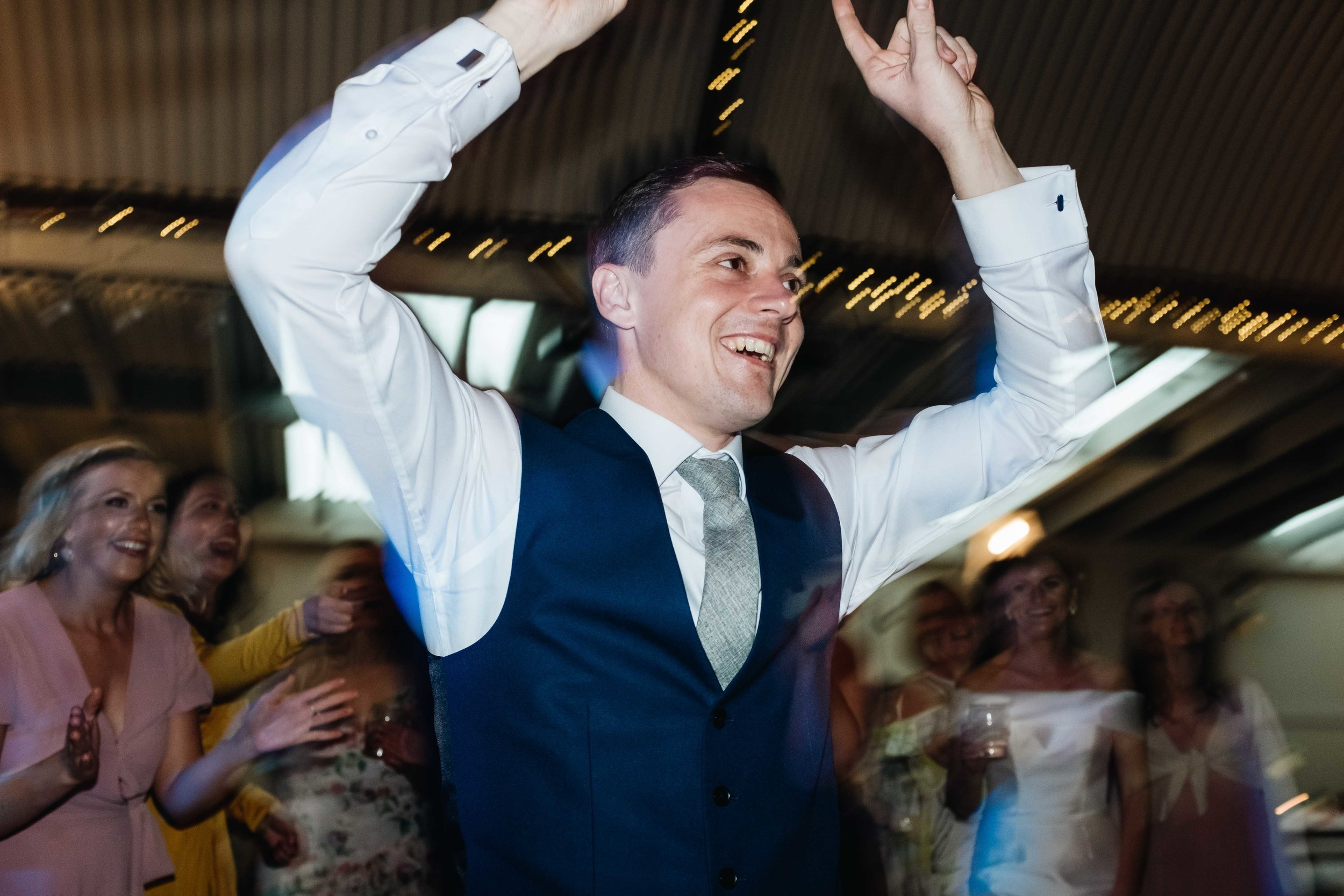 groom is dancing with his hands in the air