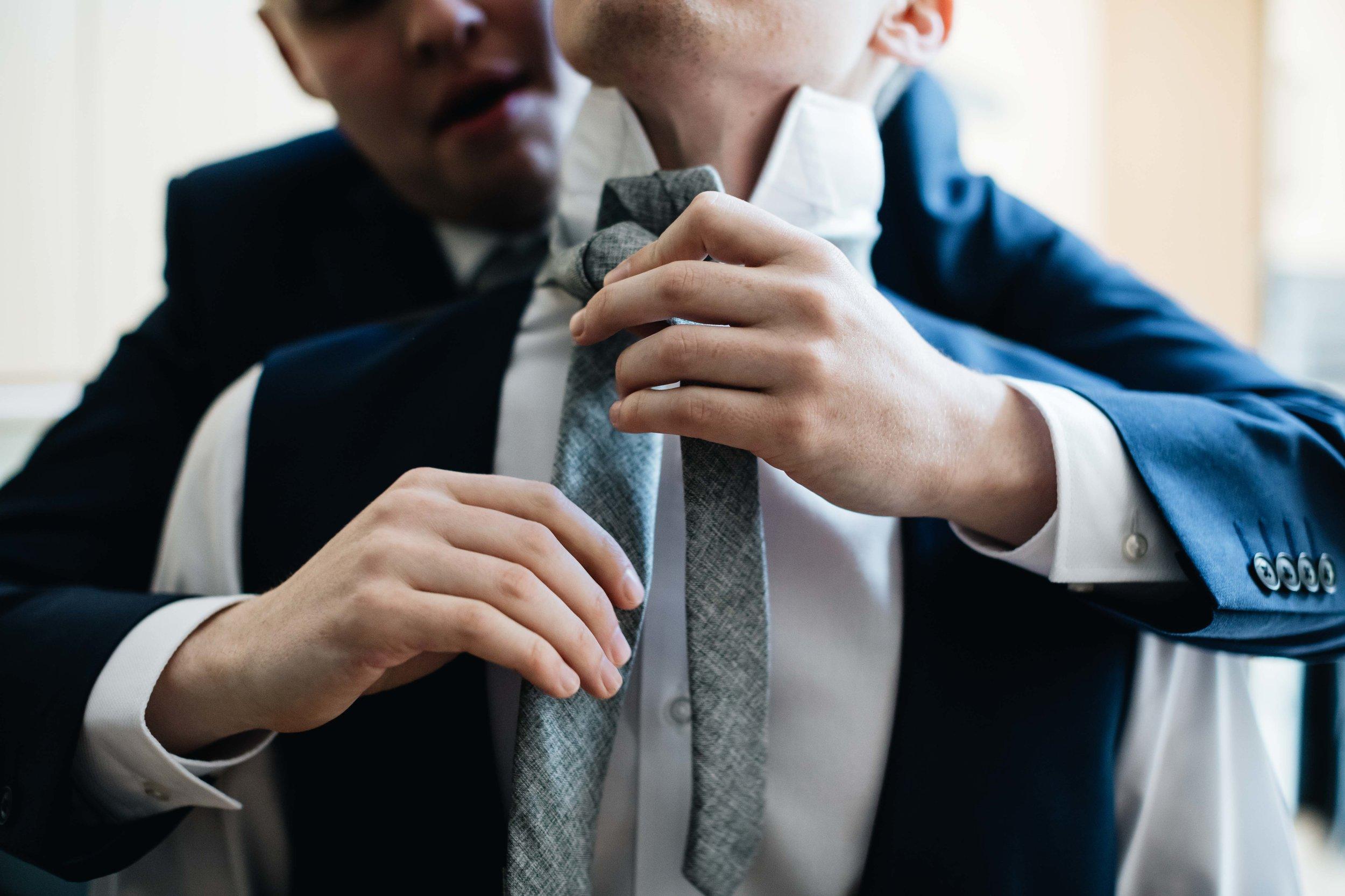 best man helping groom tie his tie