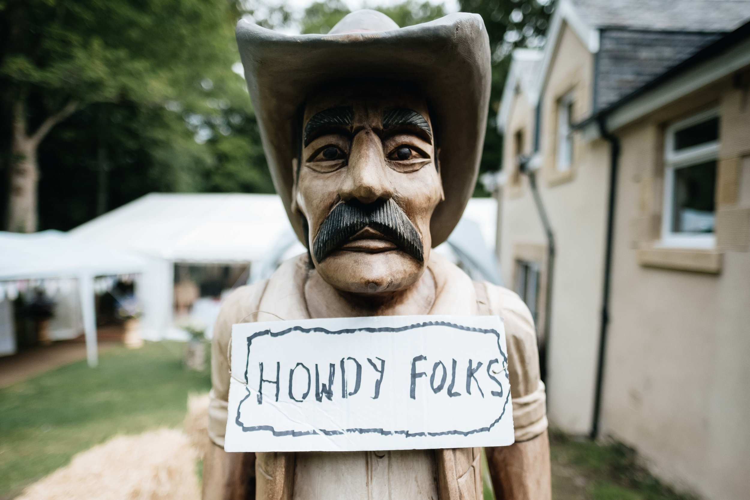 american cowboy statue with 'Howdy' sign on it
