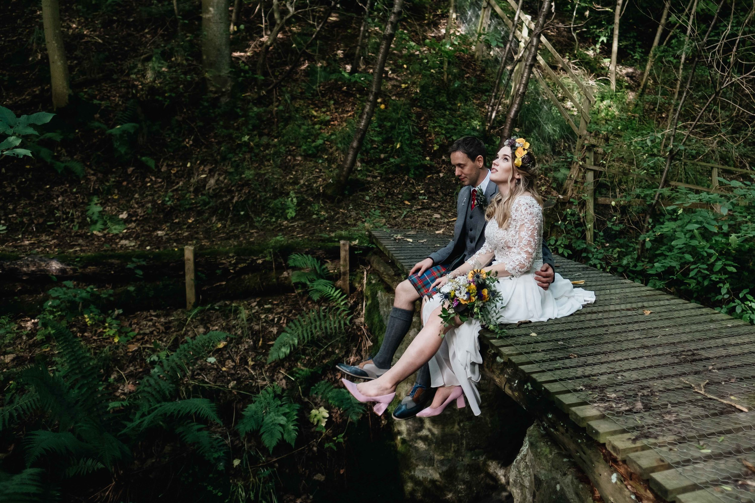 bride and groom sitting on a bridge on the groom's estate