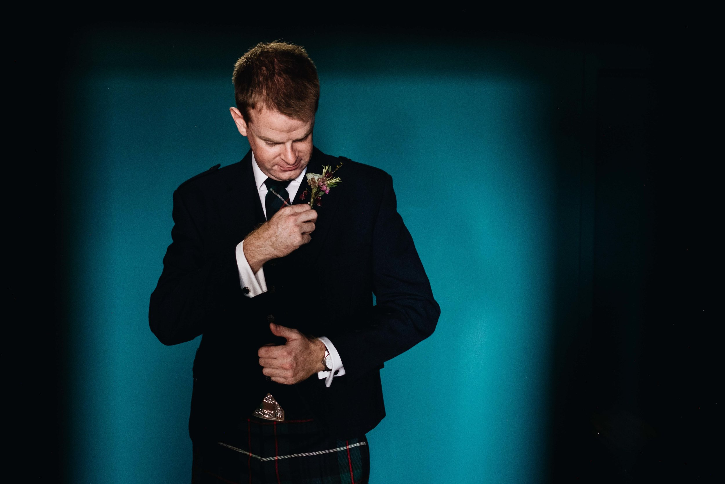 groom sorting out his button hole against a blue backdrop