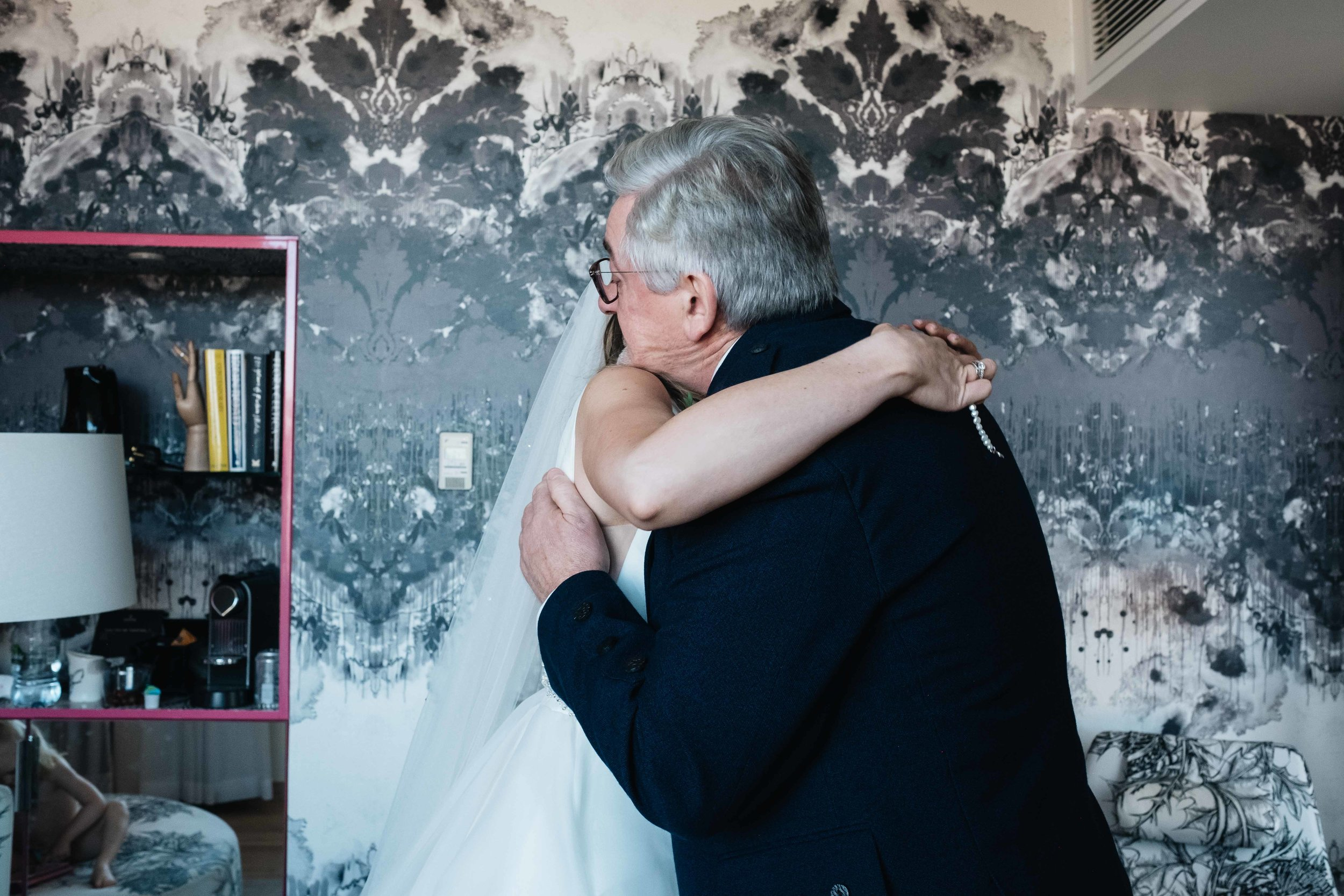 father embraces his daughter on her wedding day