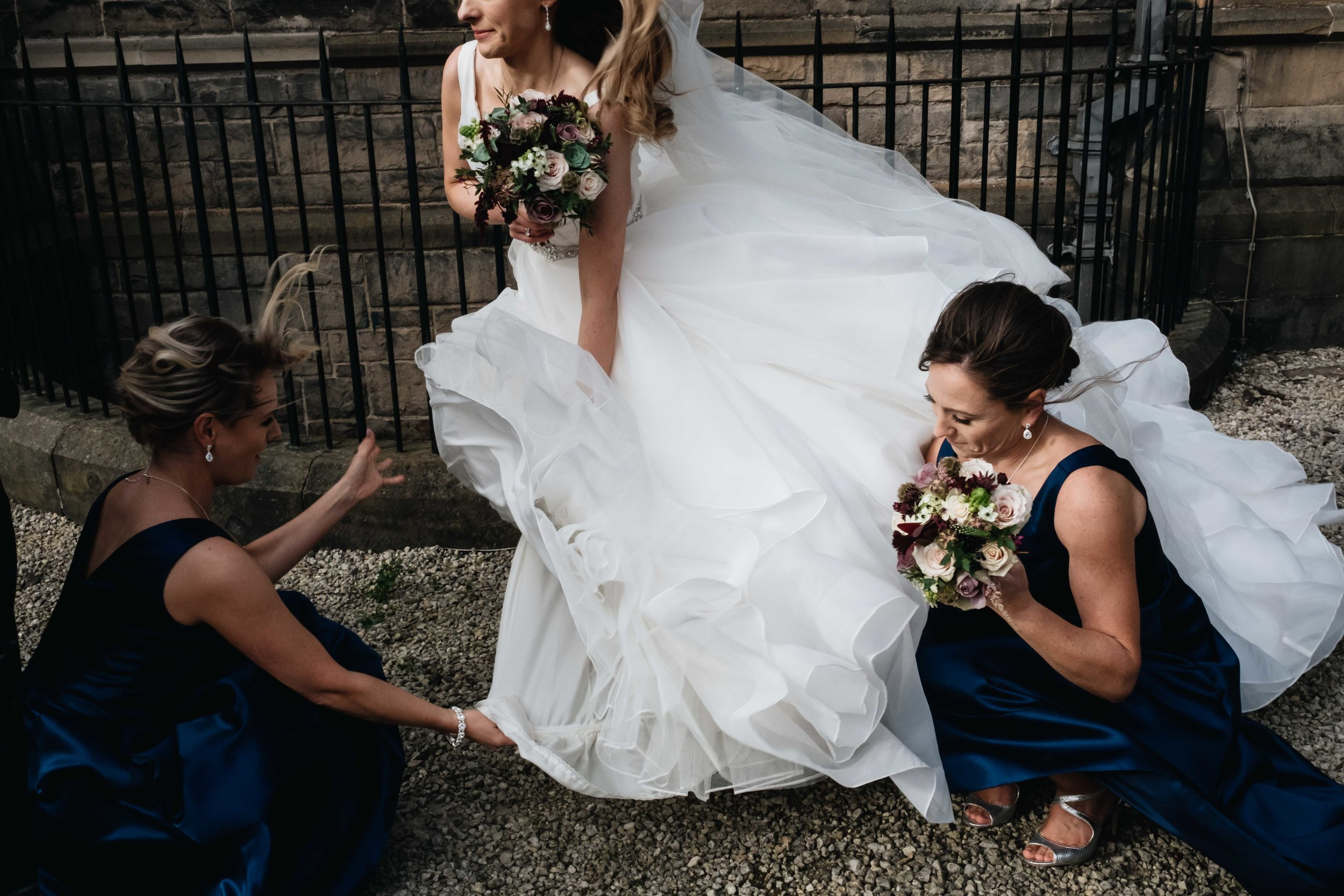 bridesmaids hold bride's wedding dress down as it blows in the strong wind
