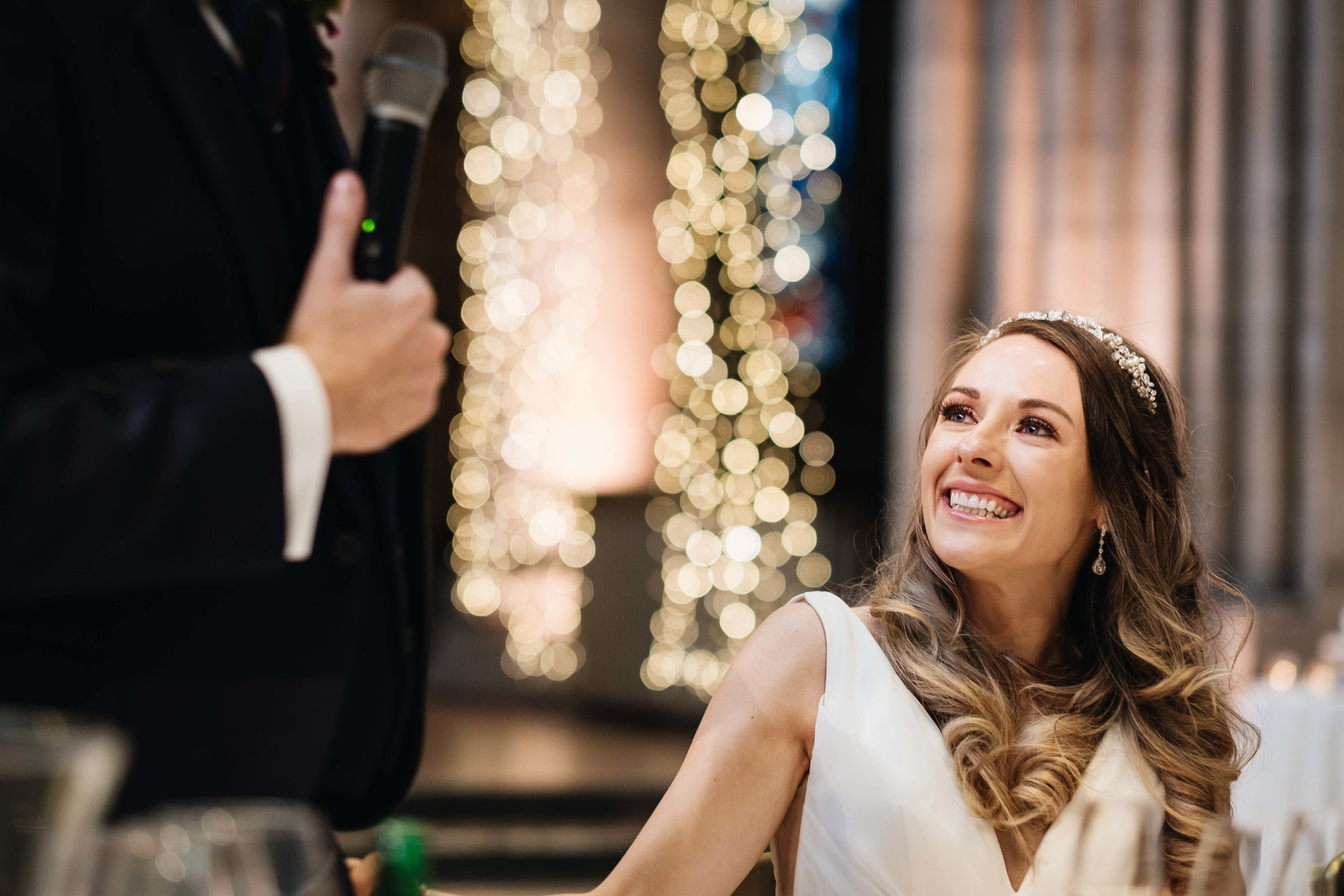 bride is smiling at her husband during his speech