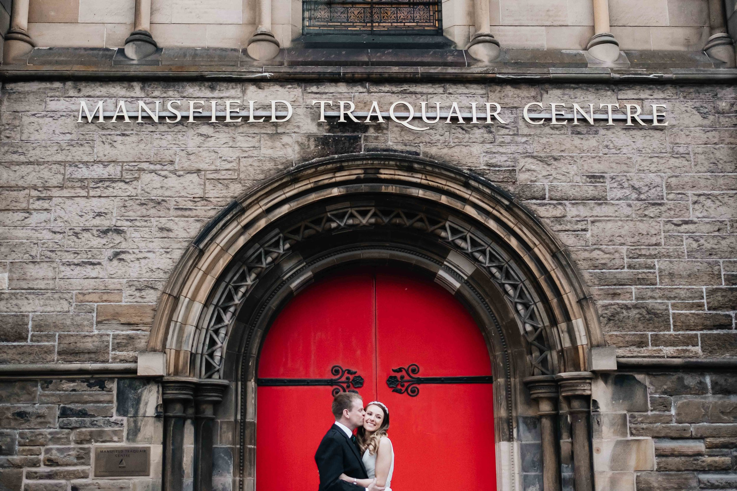 groom kisses wife outside the red doors of Mansfield Traquair