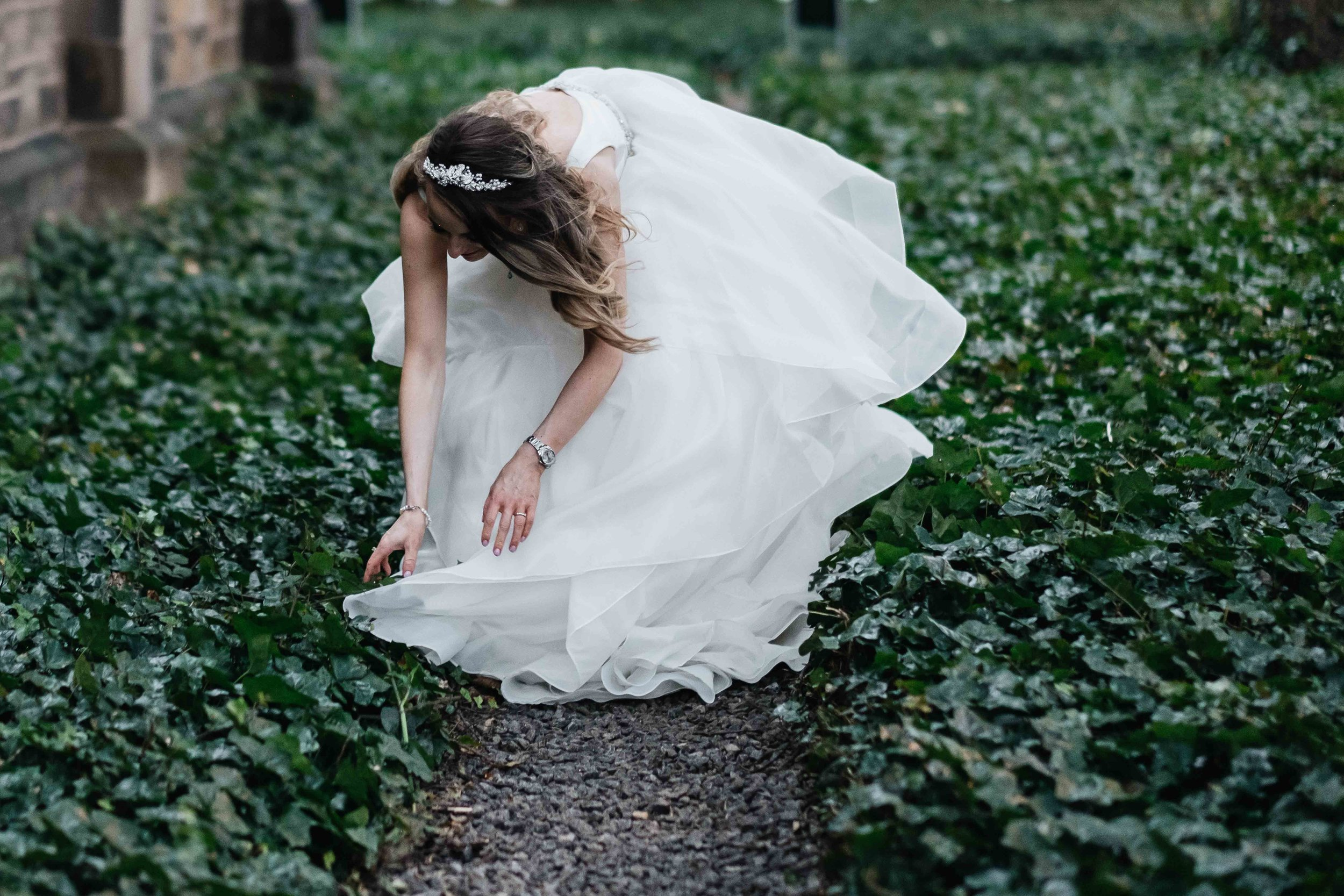 bride is bent over, detatching her dress from foliage