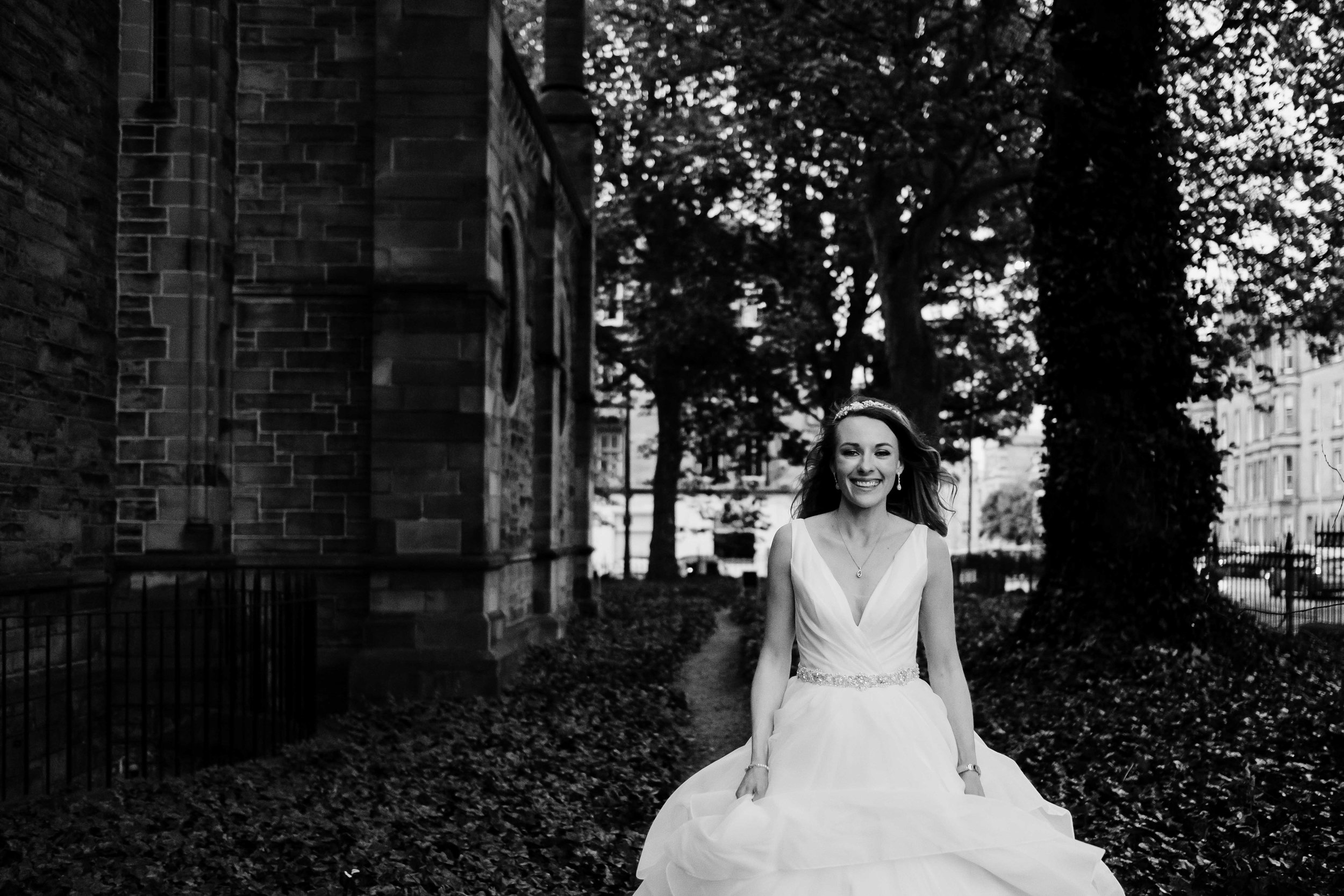 bride is walking towards the camera with a huge smile on her face