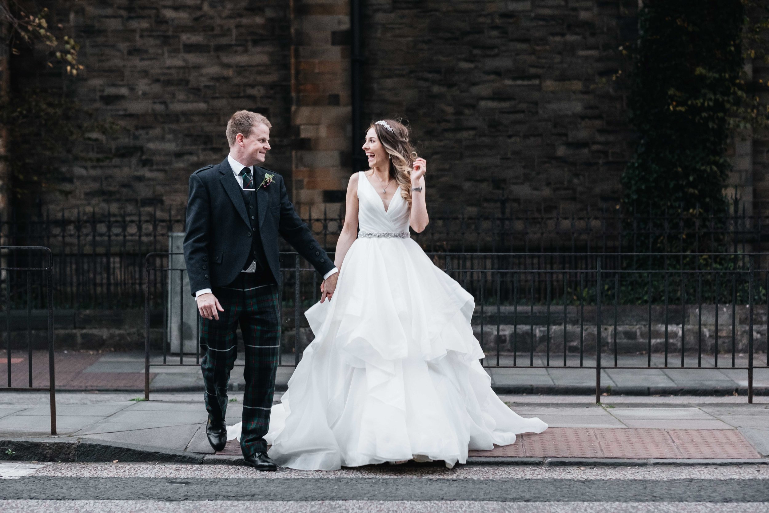 bride and groom cross the street, looking and smiling at each other