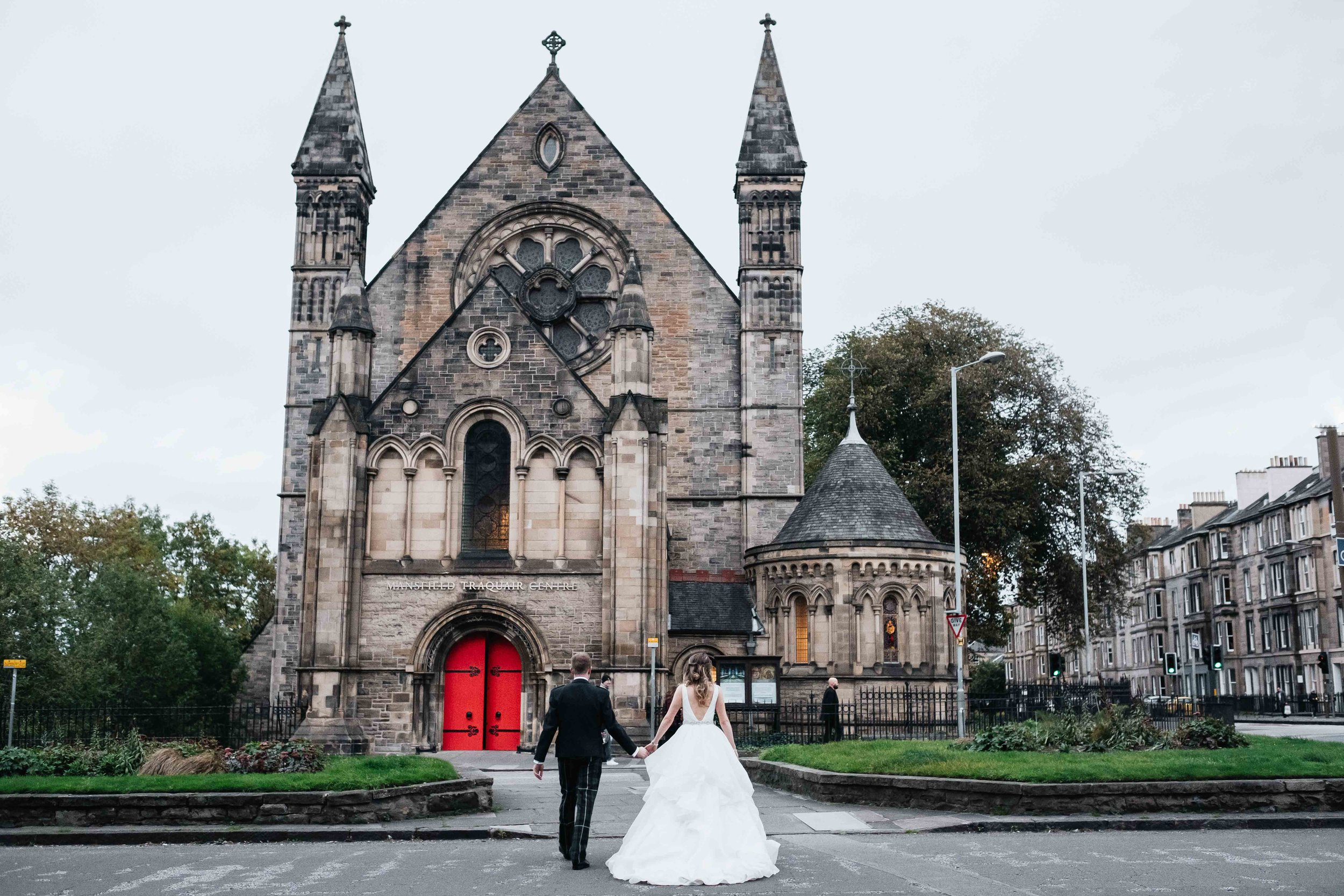 bride and groom walk across the road towards Mansfield Traquair
