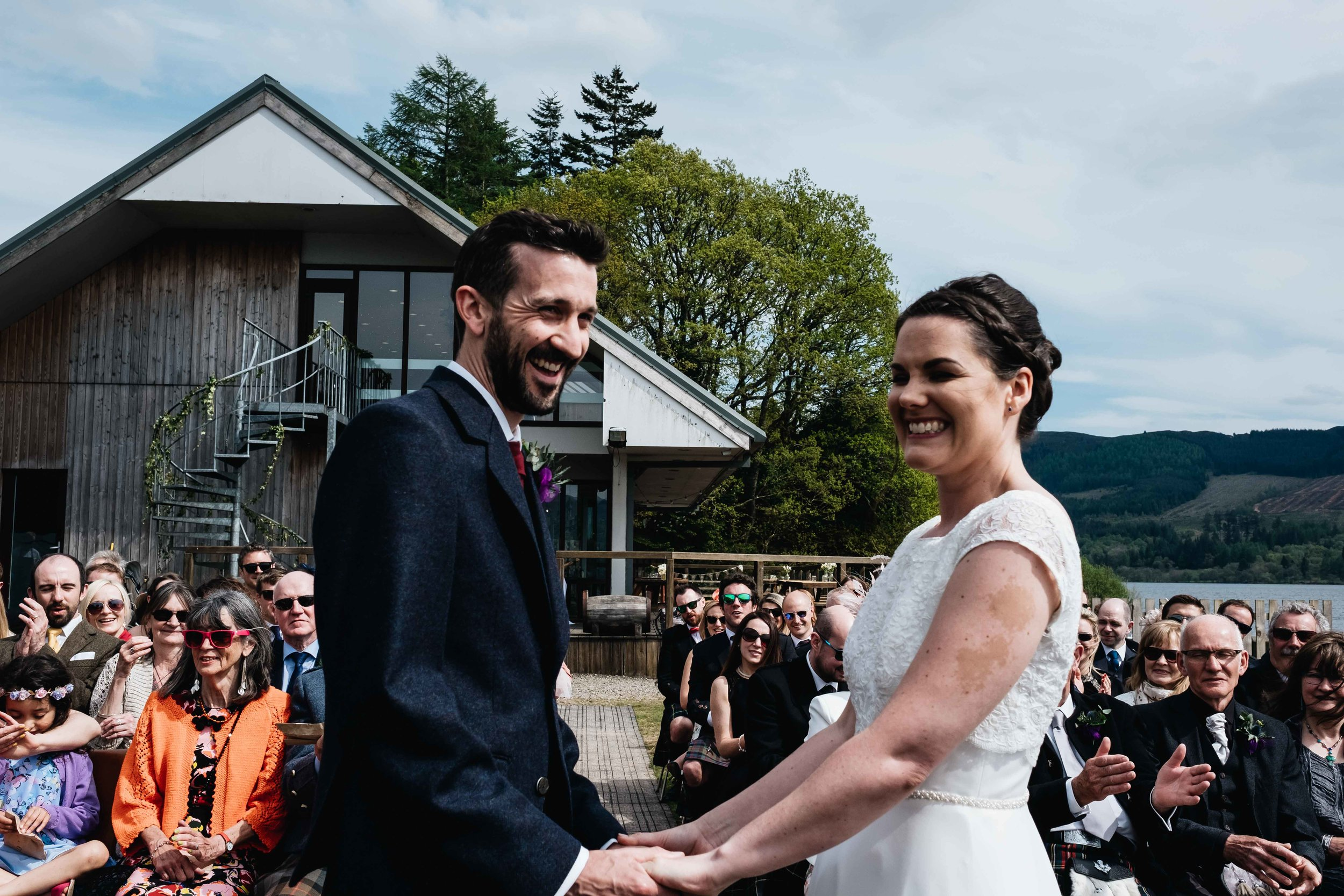 bride and groom hold hands smiling during their outdoor wedding ceremony