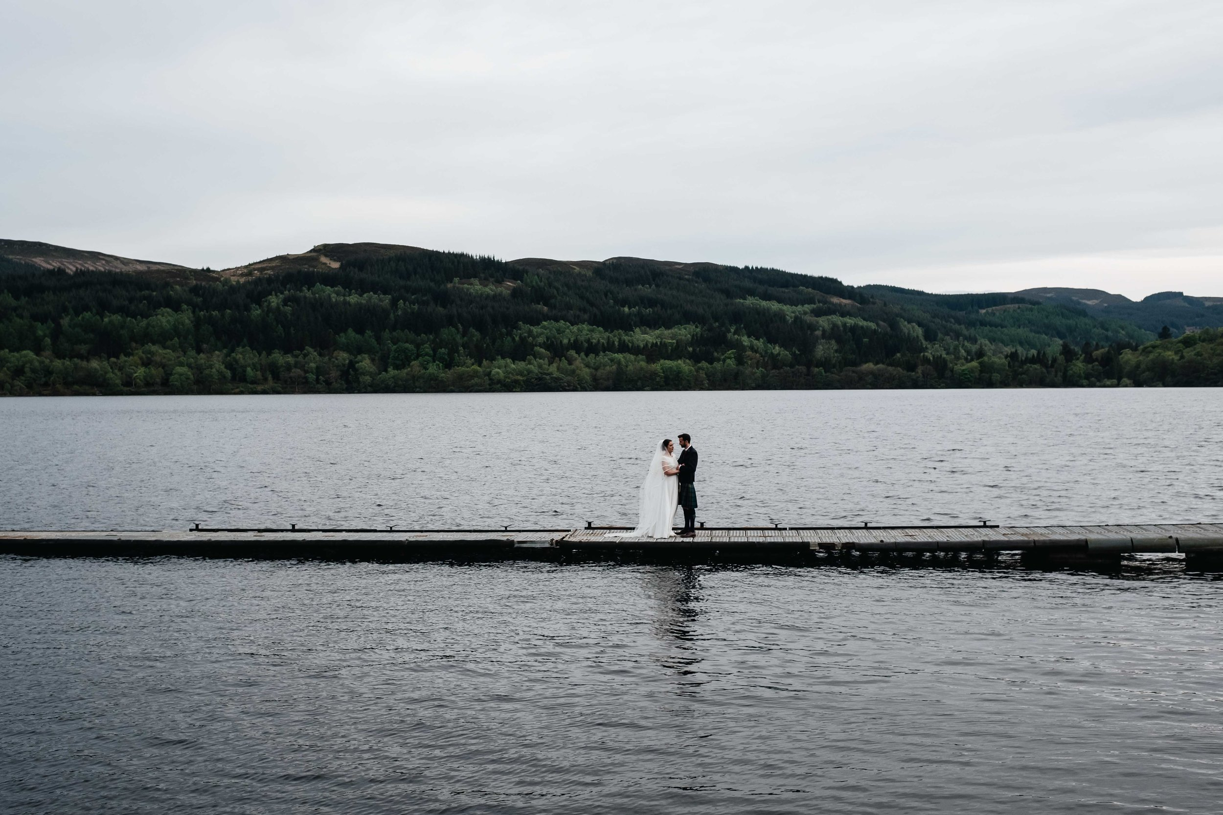 bride and groom embrace on a jetty