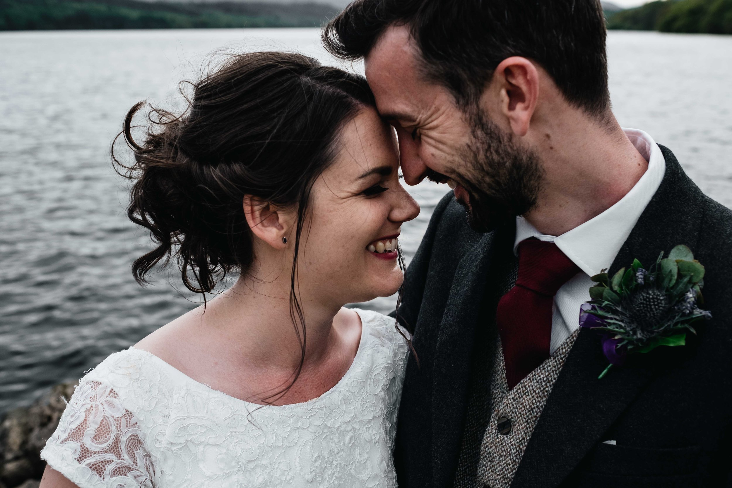 bride and groom place their heads together and smile