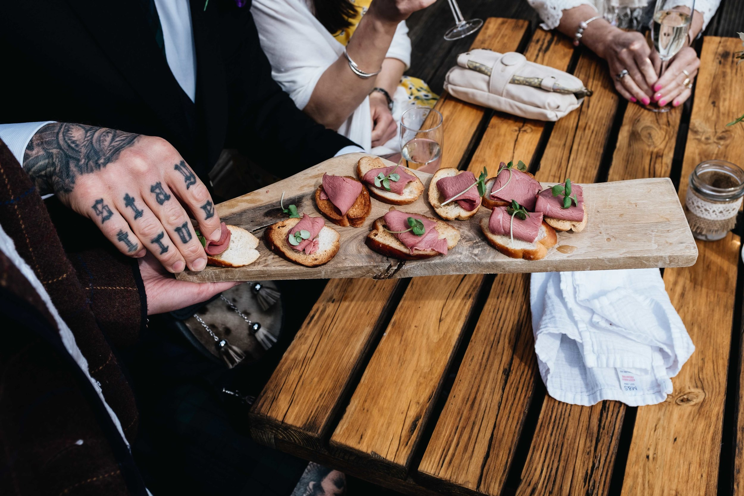 tatttoed handed guests takes canape