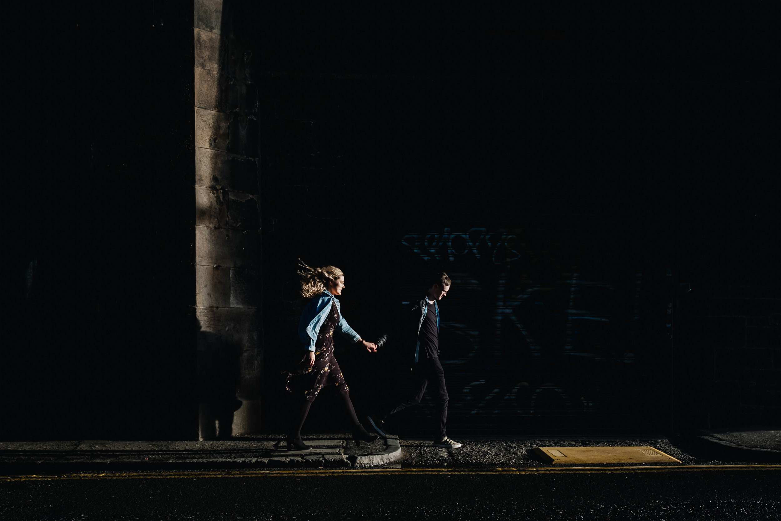 a couple are walking in shadow, holding hands with the sun falling on their faces.