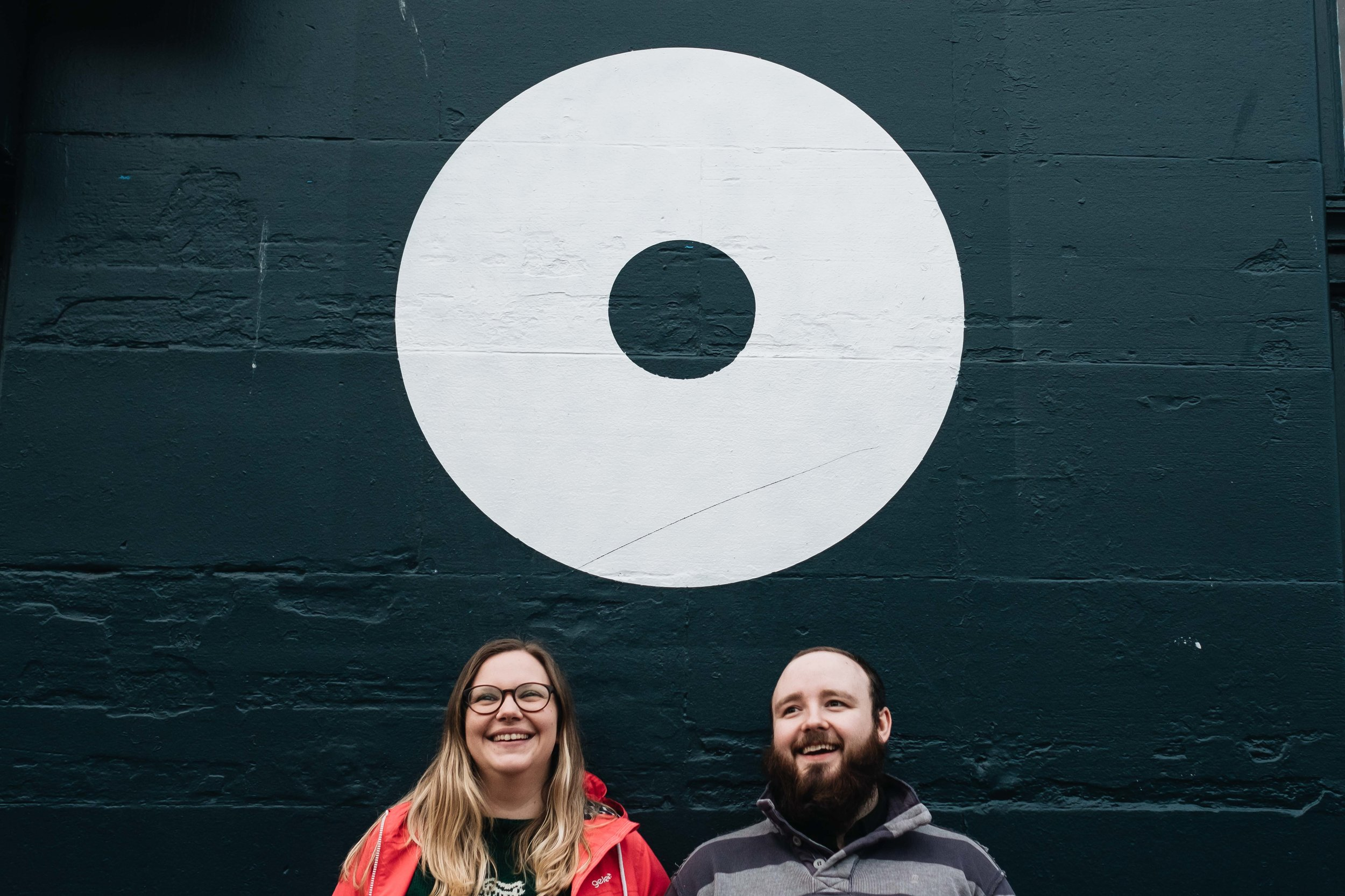 a couple stand by a large circular wall and looking happy
