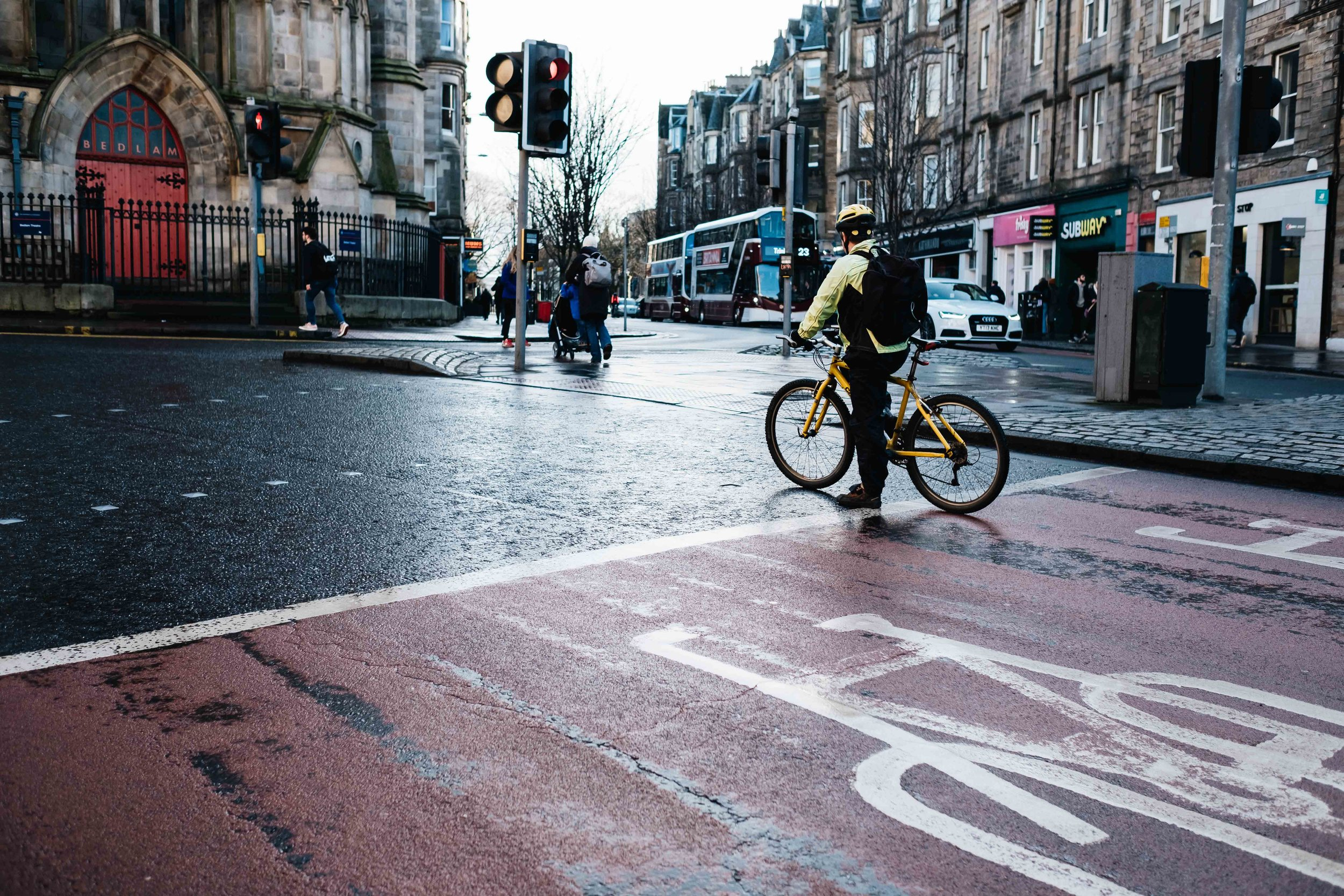 a cyclist is stopped at a red light in a busy Edinburgh street