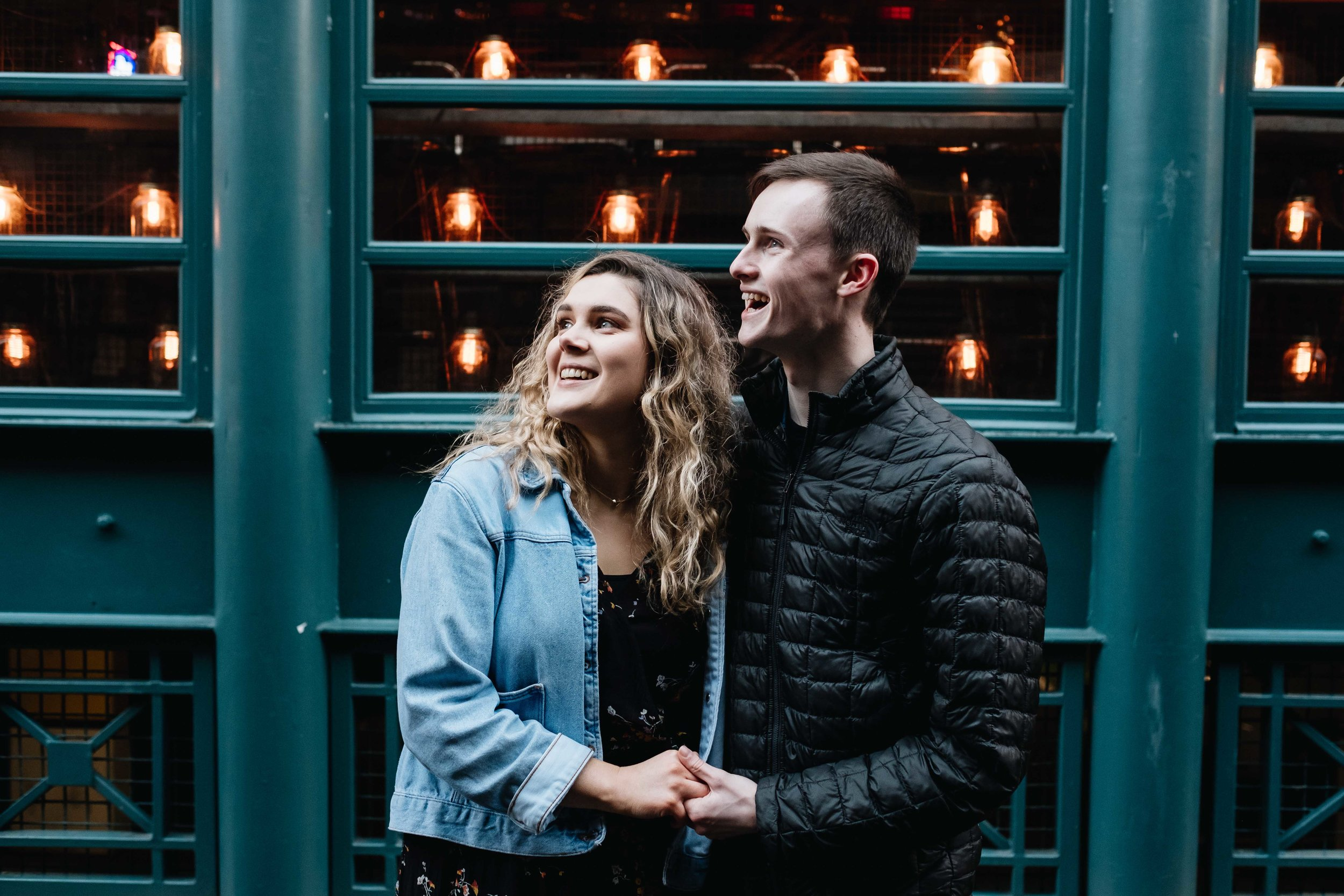 A happy smiing couple in an embrace with green wall and lights behind them.