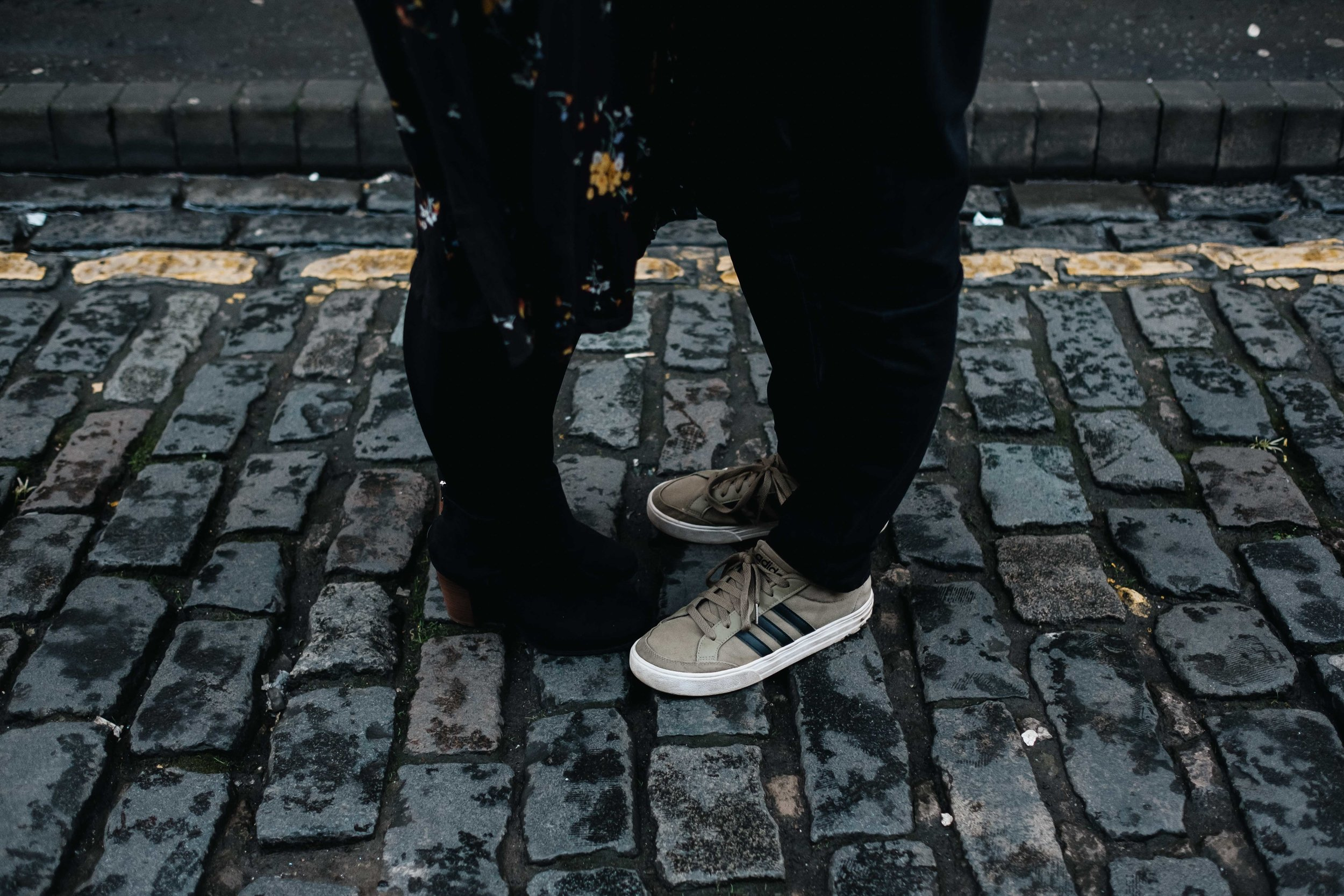 A couple's feet only are in view. They are standing close to each other on a cobbled street.