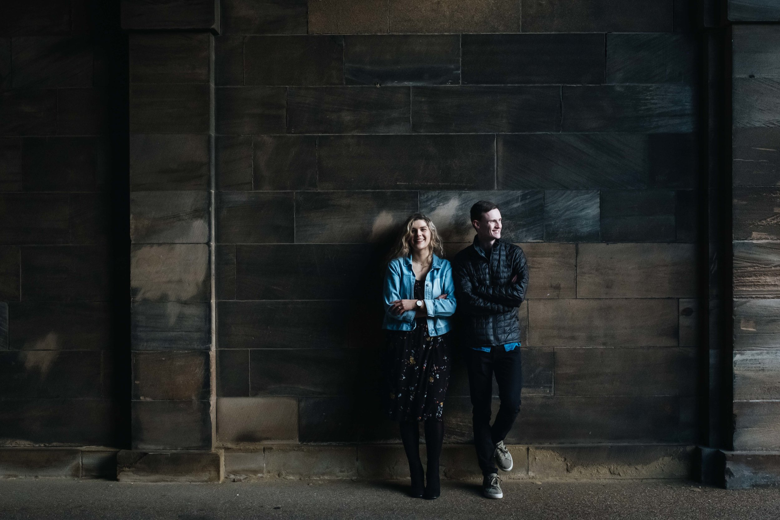 An engaged couple lean against a wall at Edinburgh University, smiling.