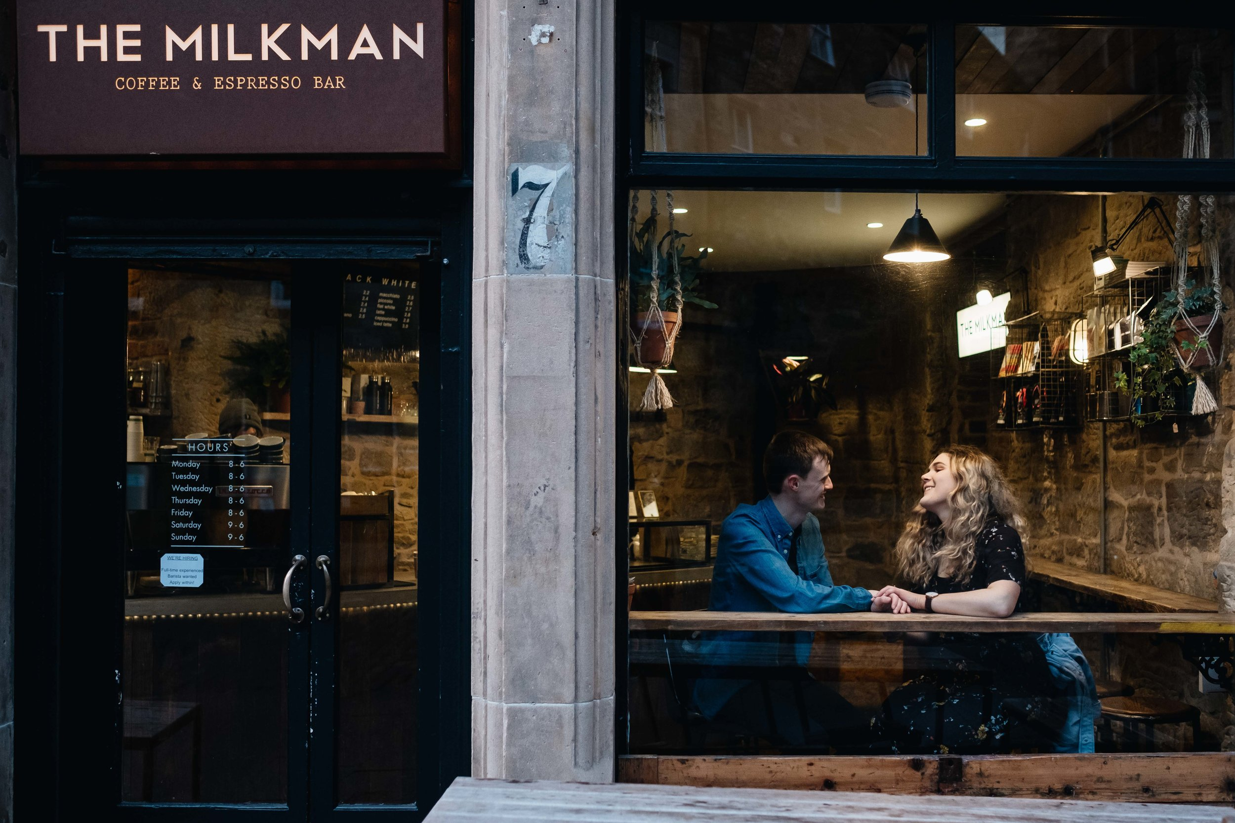 An smiling engaged couple sit inside The Milkman coffee shop n Edinburgh.