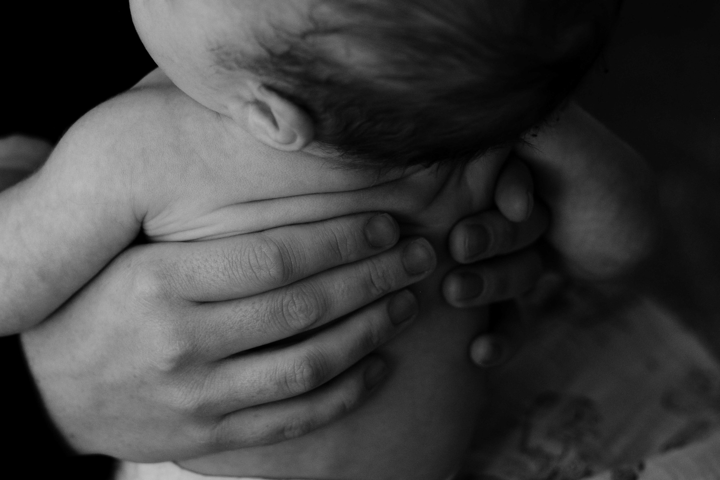 A close up photo of a mother's hand which is holding her small child