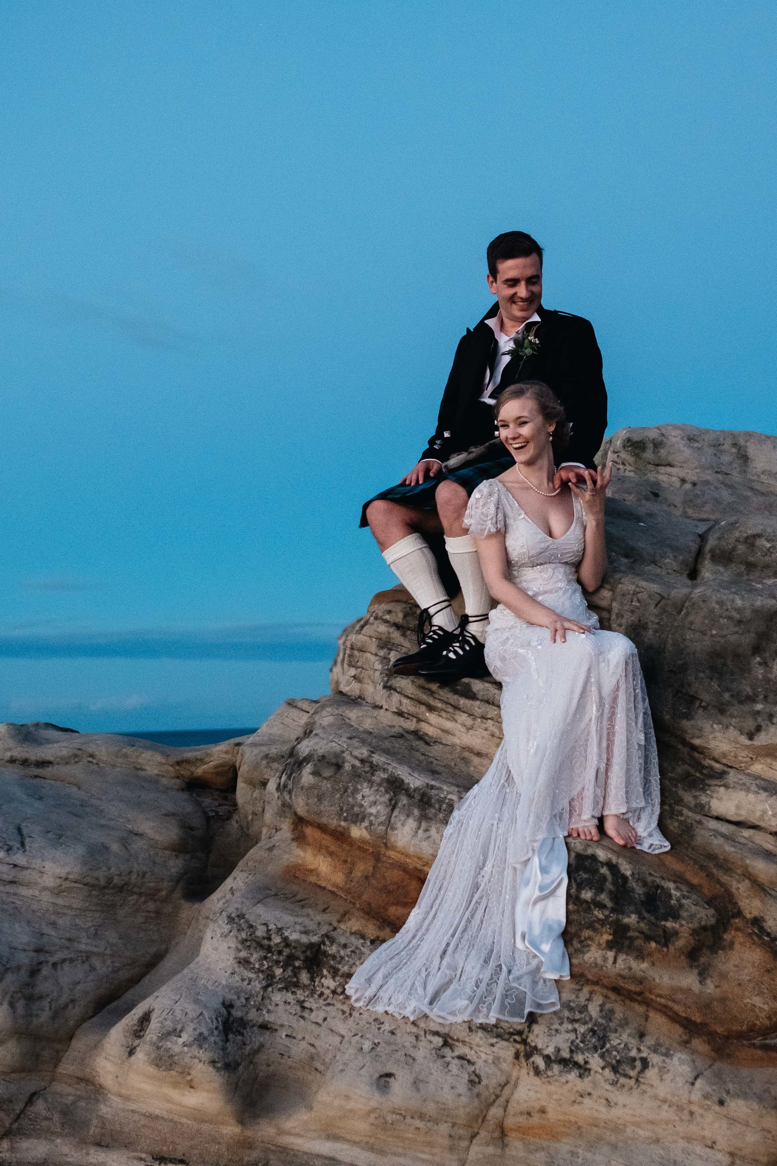 A bride and groom are sitting on a rock.