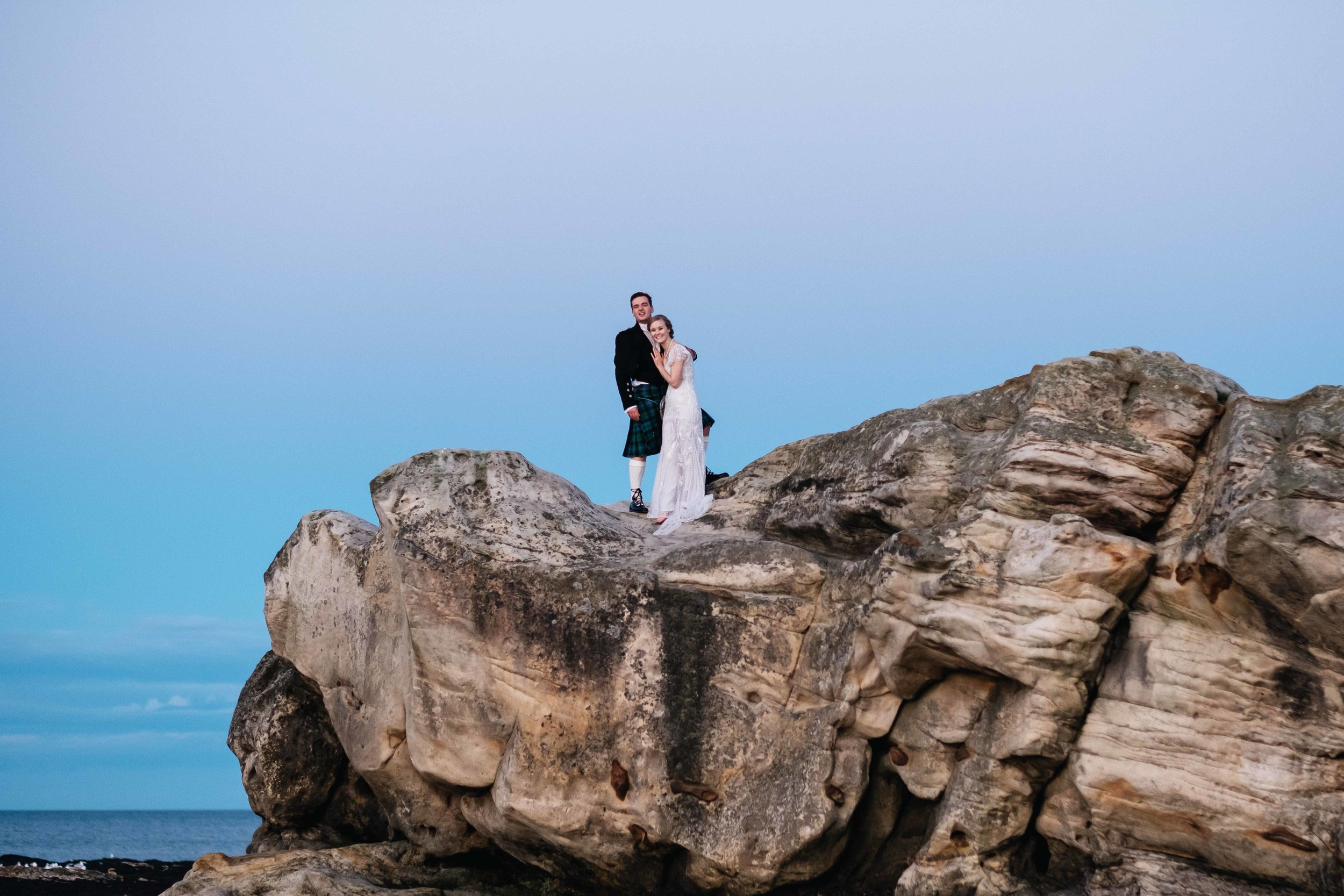 A bride and groom embrace whilst standing a very large rock in the middle of the beach.