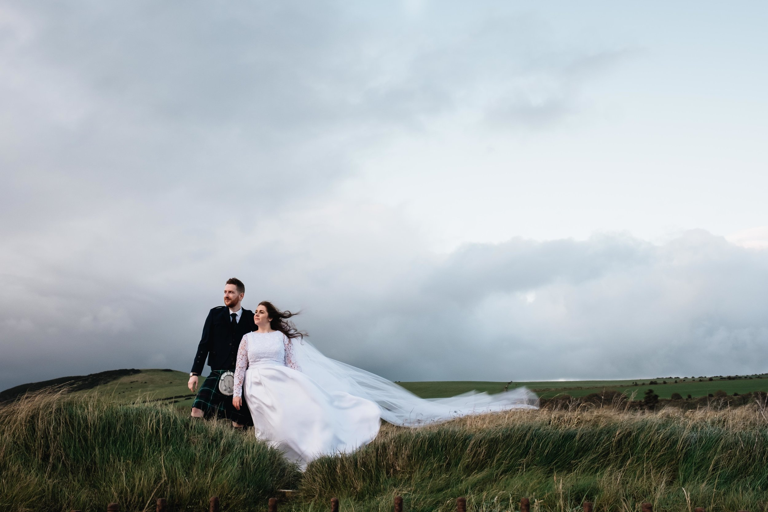A bride and groom stand in the wind during their elopement