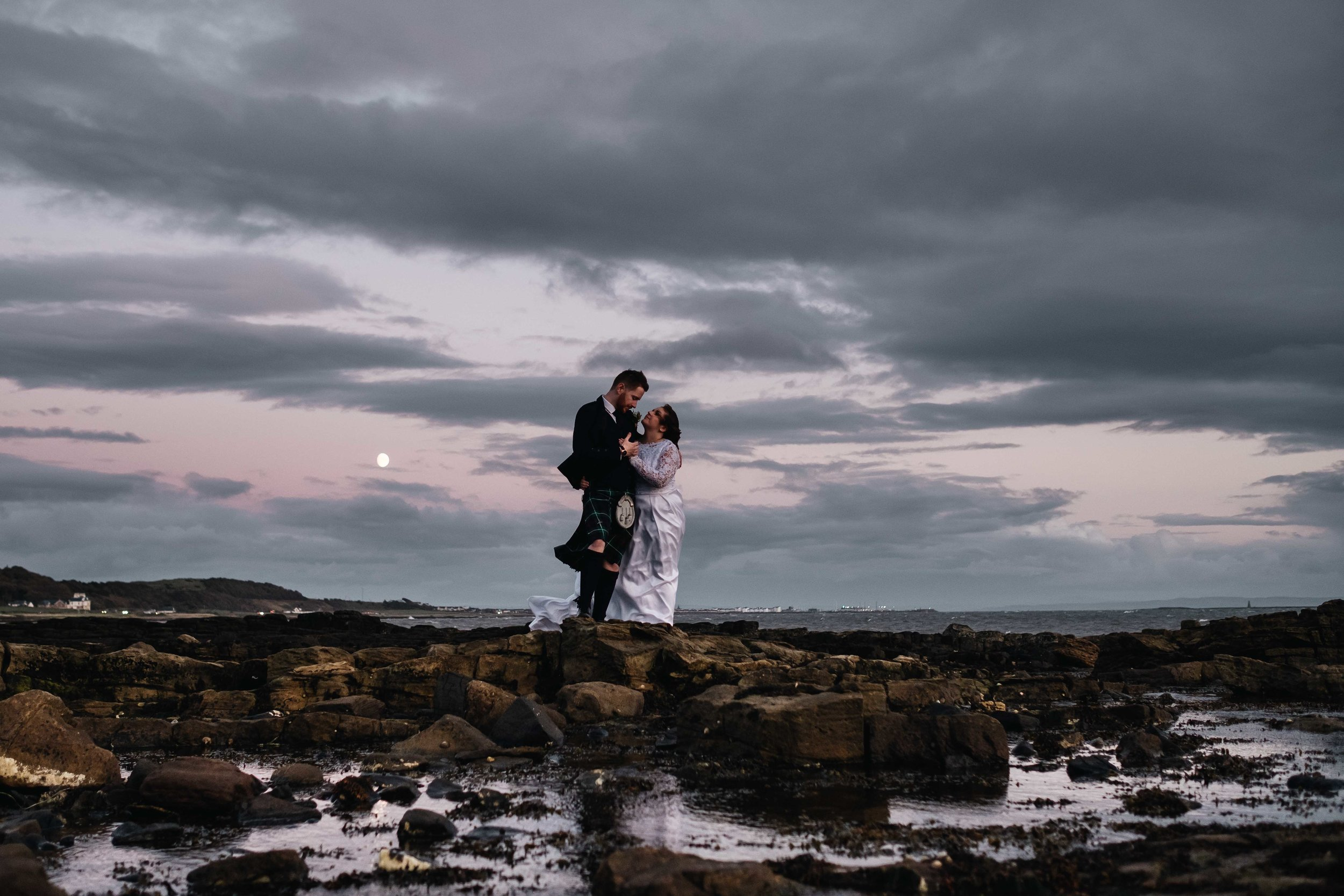 A bride and groom stand on a rock at night embracing at the beach and the moon is high in the sky