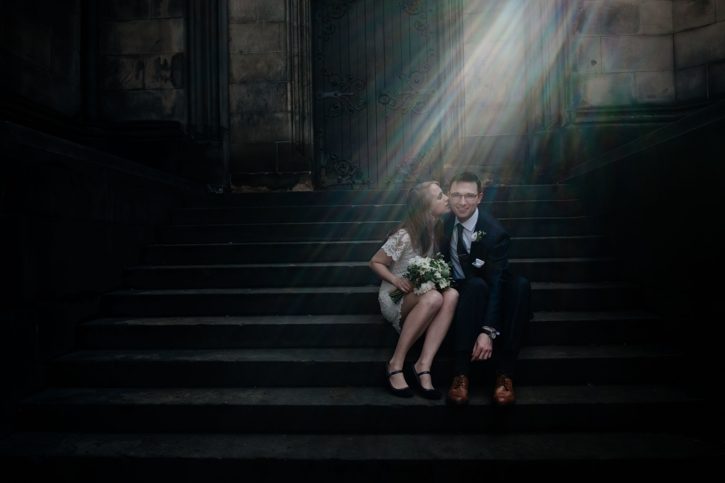 A bride and groom sitting on the stairs outside St Giles, Edinburgh.