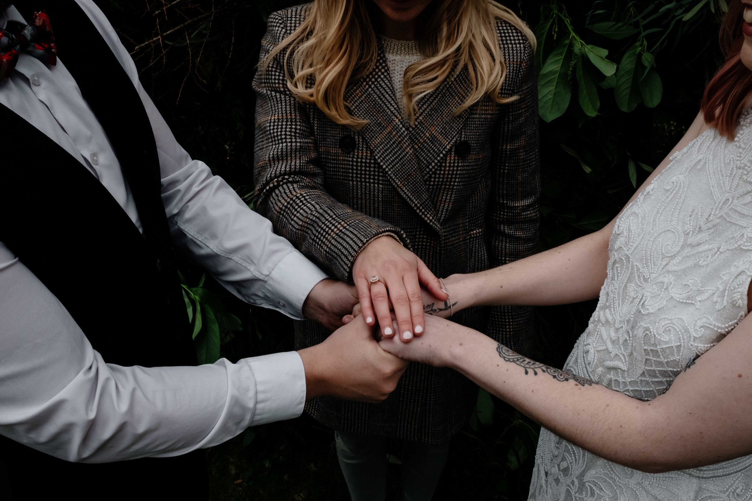 A close up shot during the wedding ceremong of an elopement and the celebrant's hands are on top of the couples.