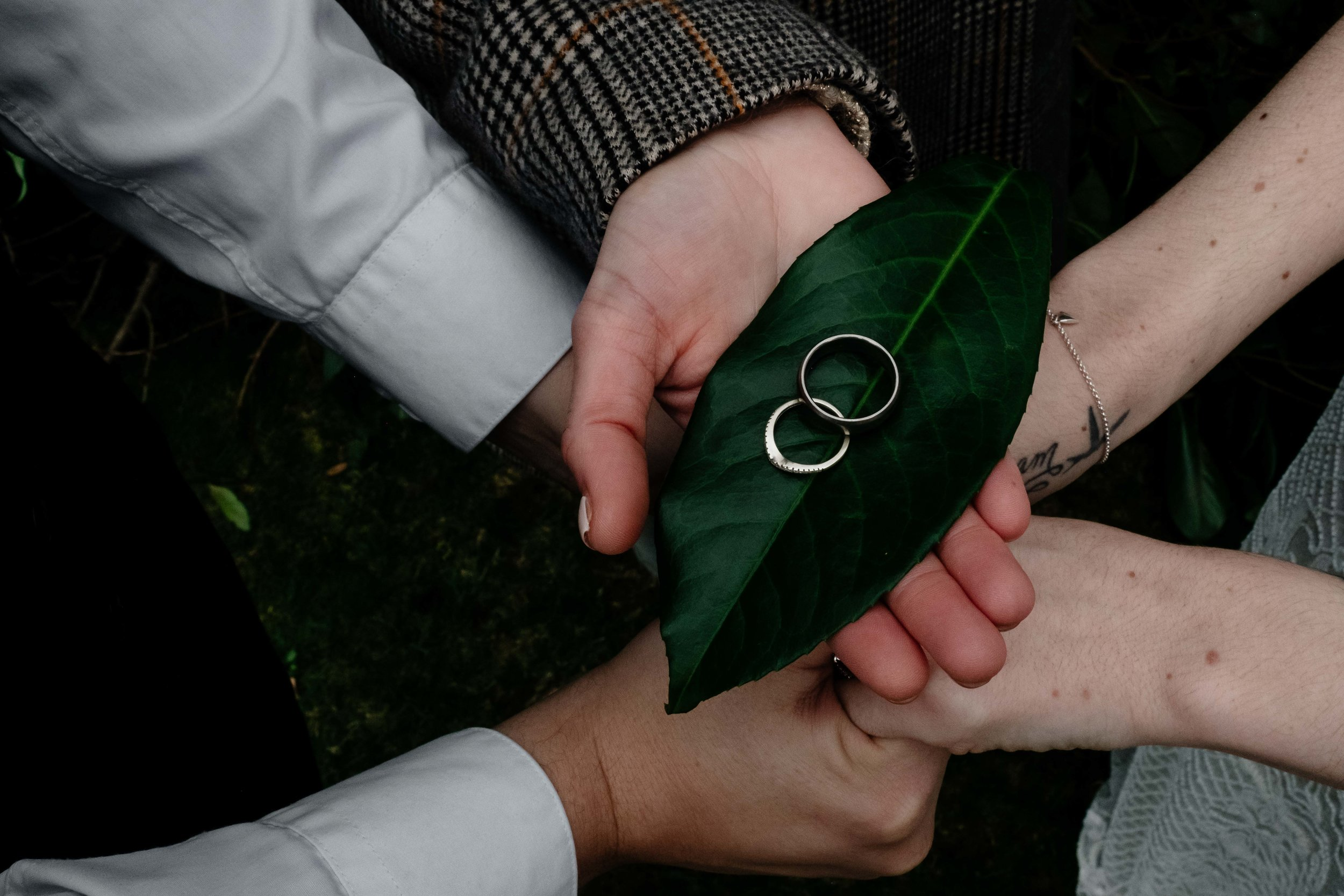 The celebrant holds the wedding bands out which are placed on a large leaf.