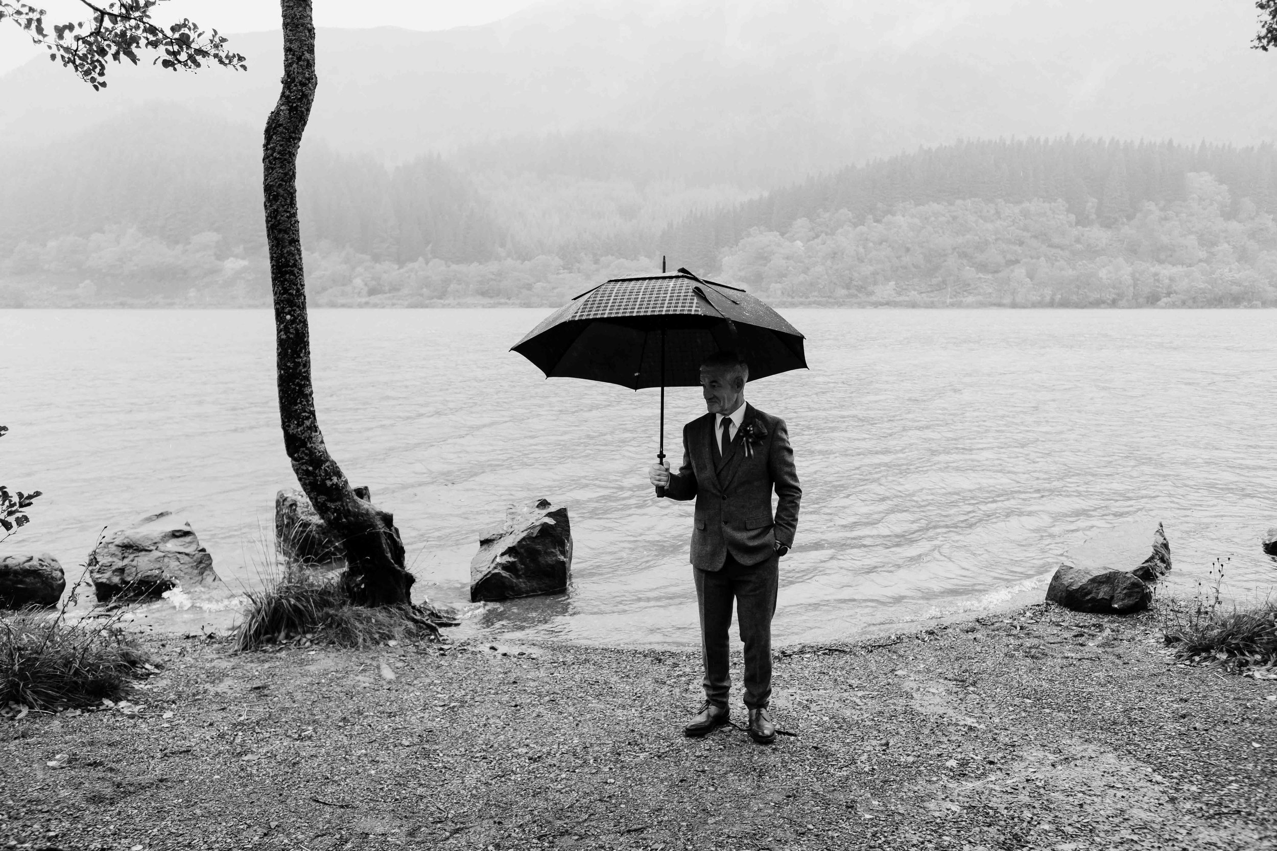 A groom stands underneath his umbrella during his lochside elopement
