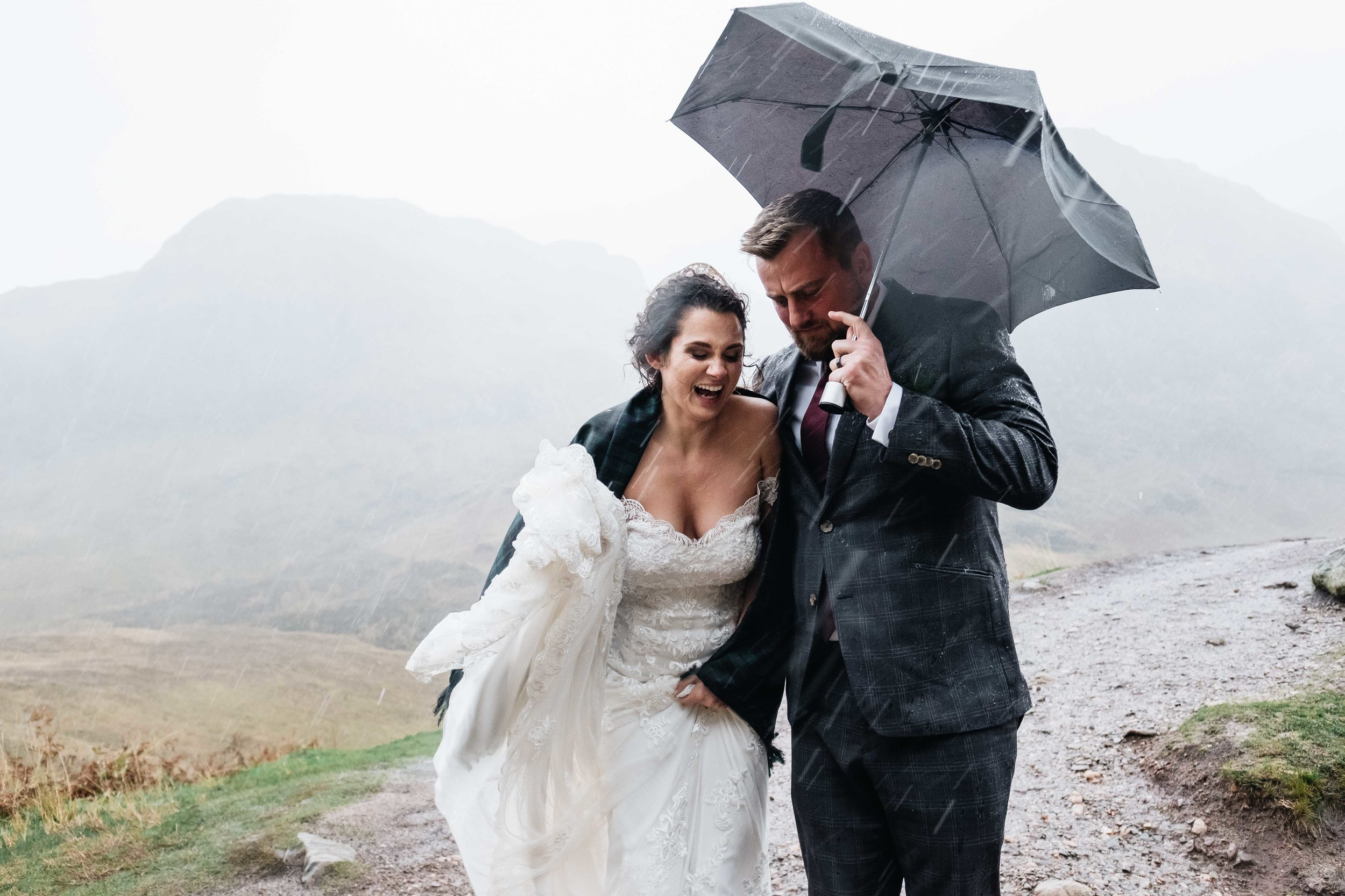 A bride and groom walk in torrential rain .The groom holds an umbrella but it's clear the wind is too heavy to protect them.