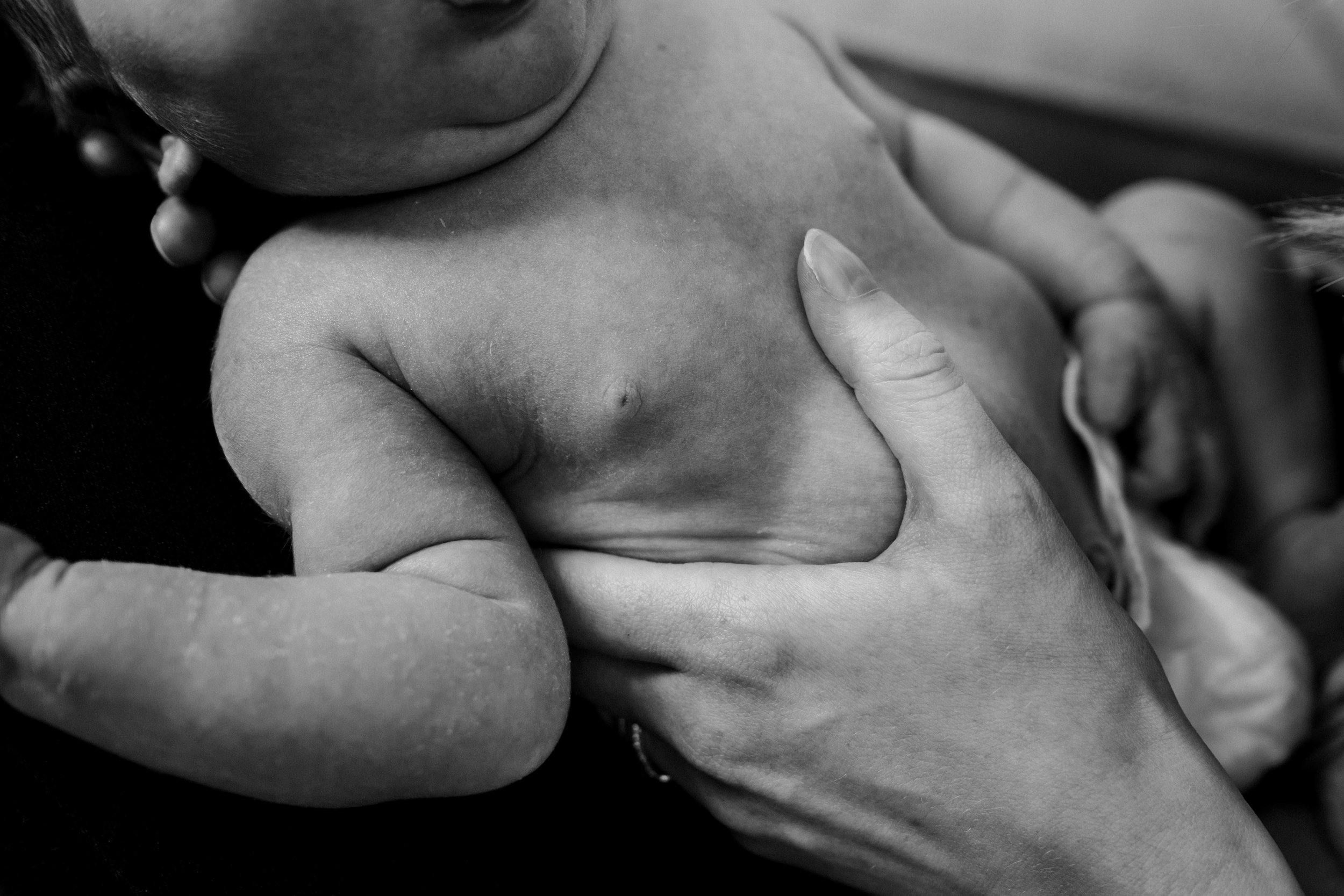 A close up shot of a mother's hands on her baby.