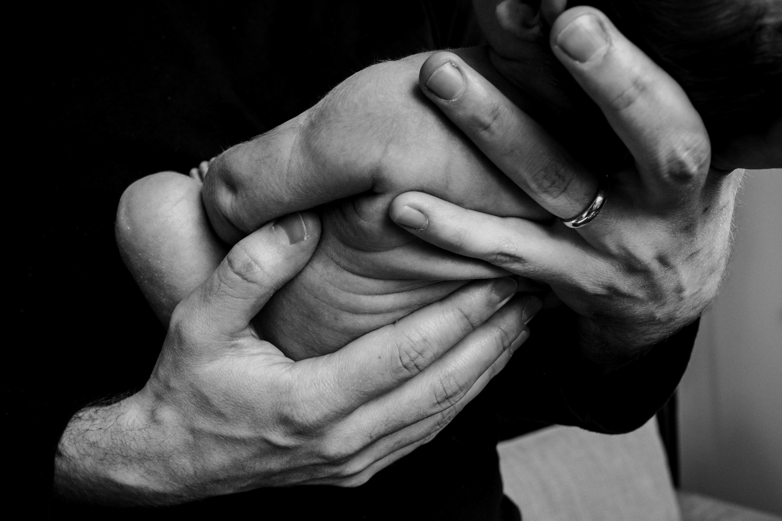 A father holds his tiny newborn daughter in his large hands.