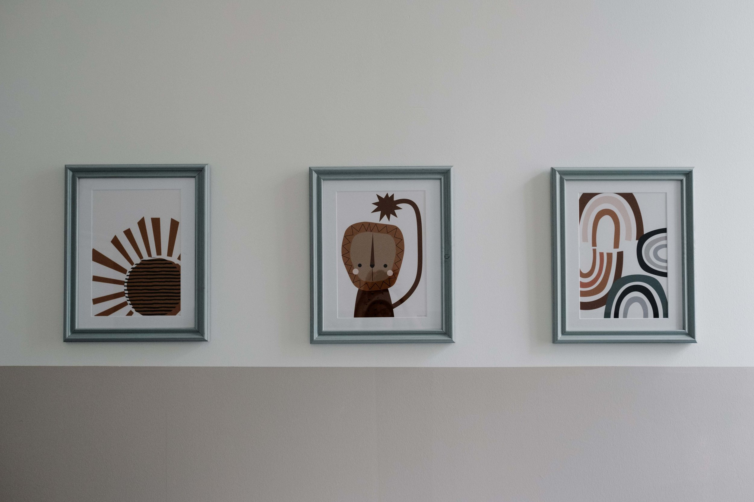 Three paintings hang in a row on the walls of a baby's nursery.