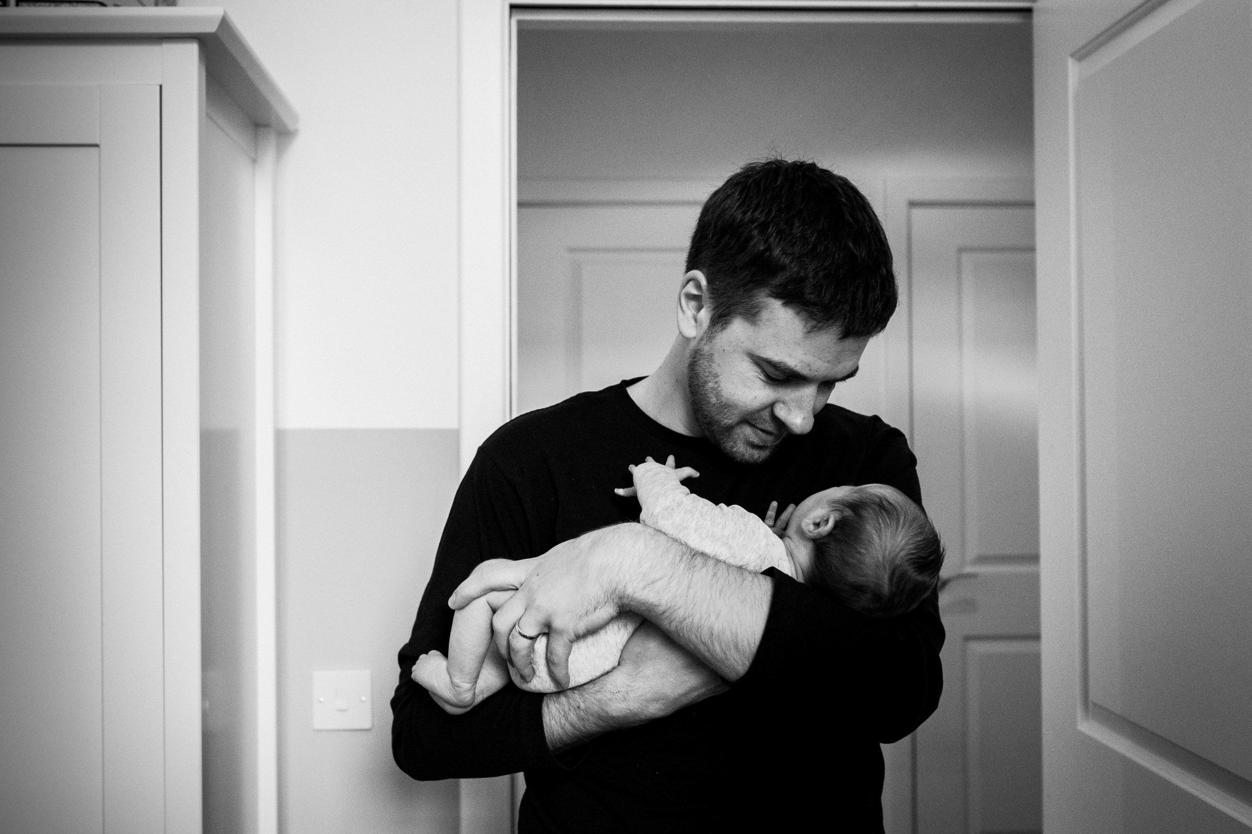 Father stands in the doorway holding his baby girl.