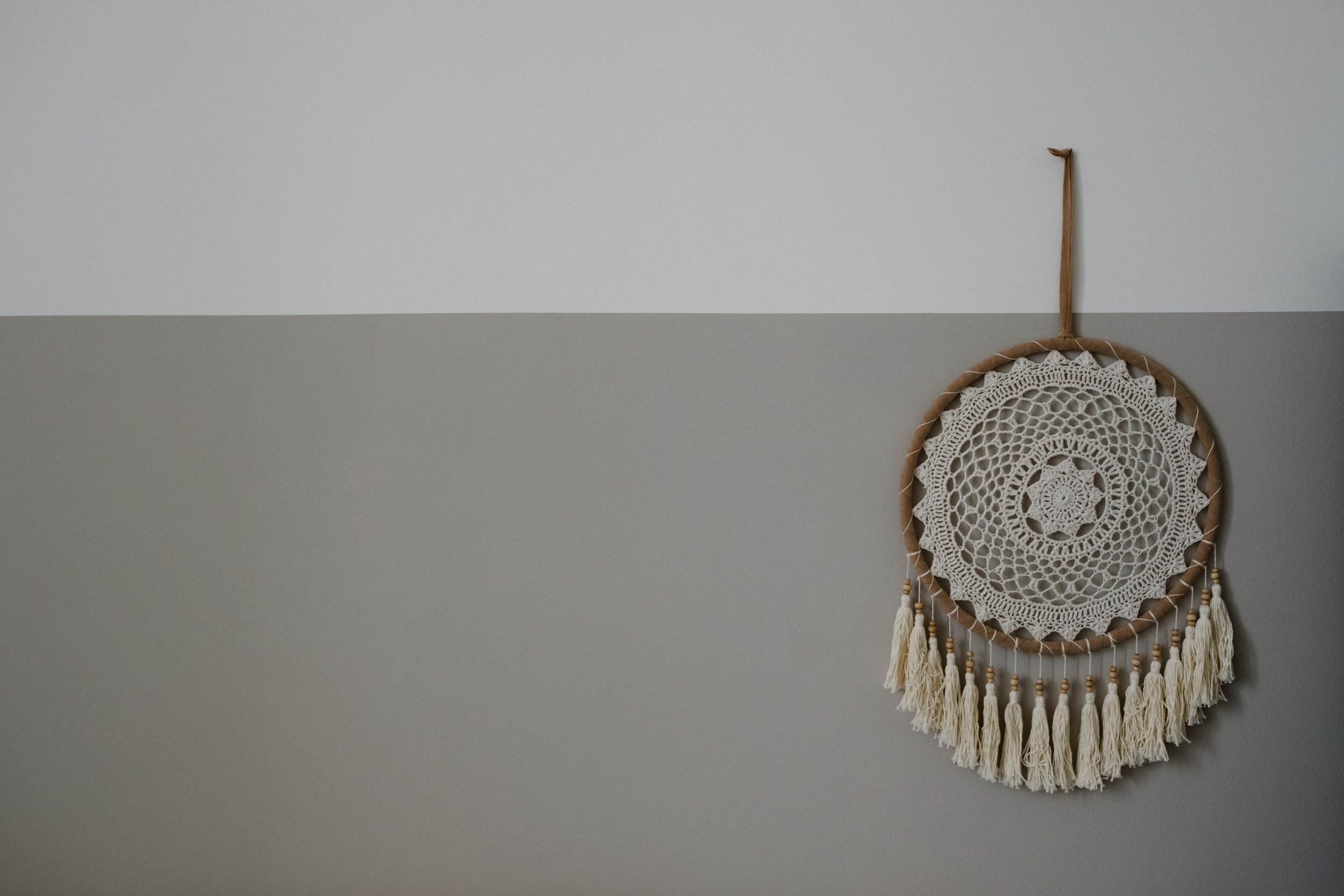 A dream catcher hangs on the wall of a baby's nursery.