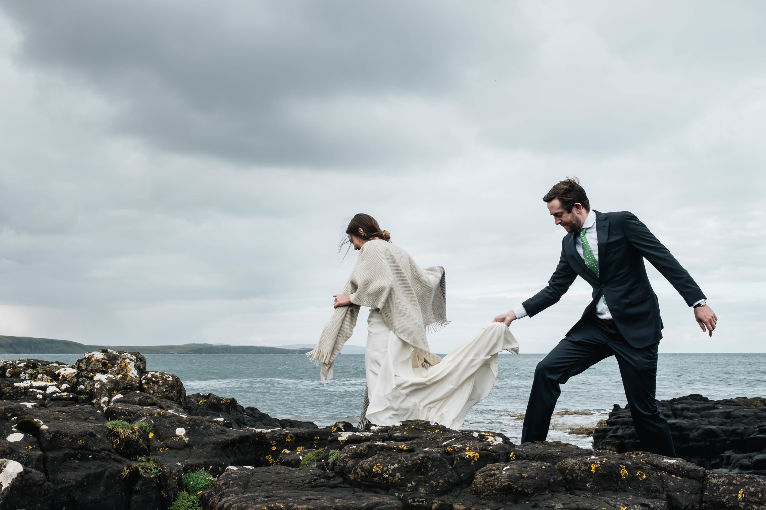 groom helping his bride by holding her dress as they walk on the rocks