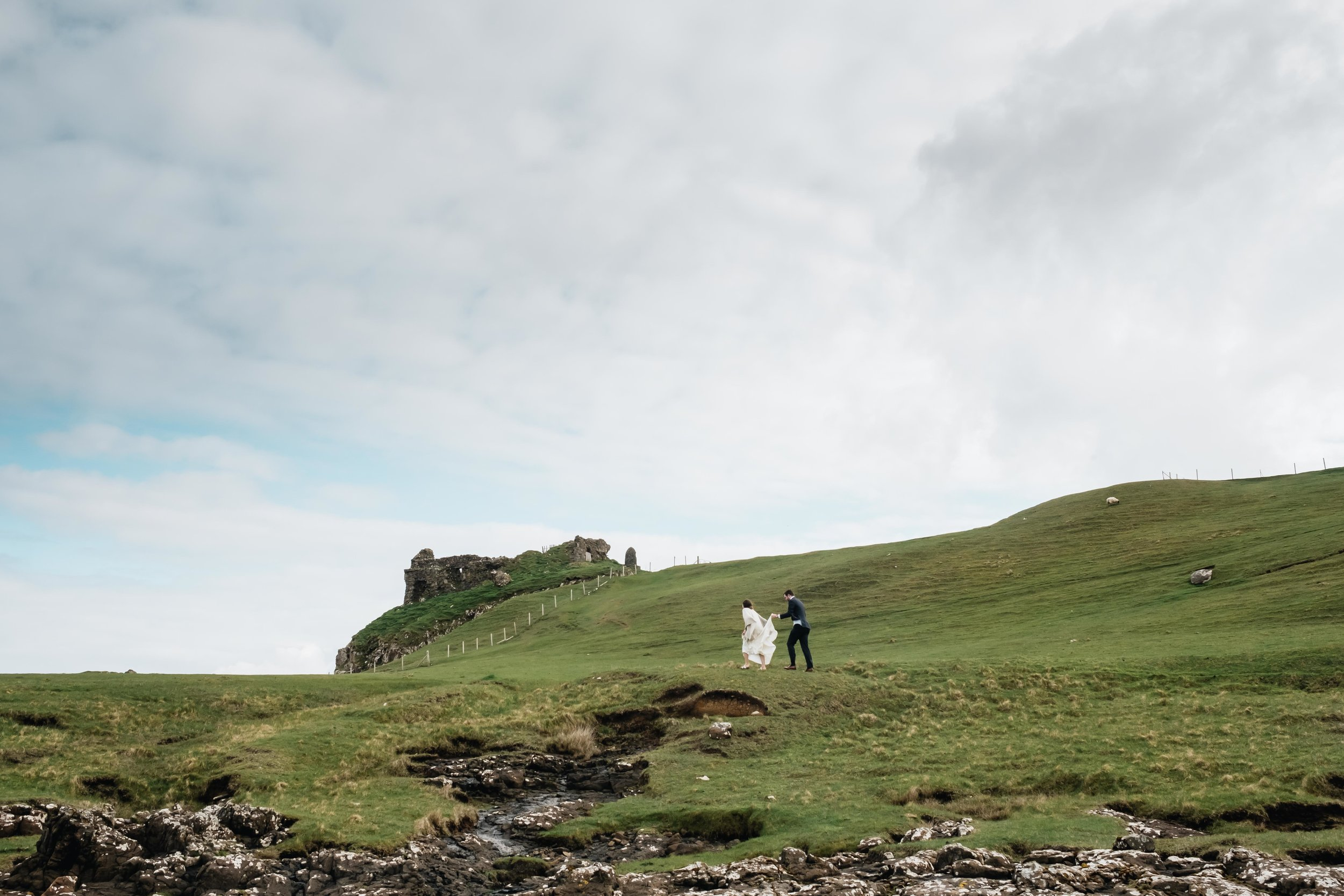 Couple walking up the hill to Duntullum Castle.